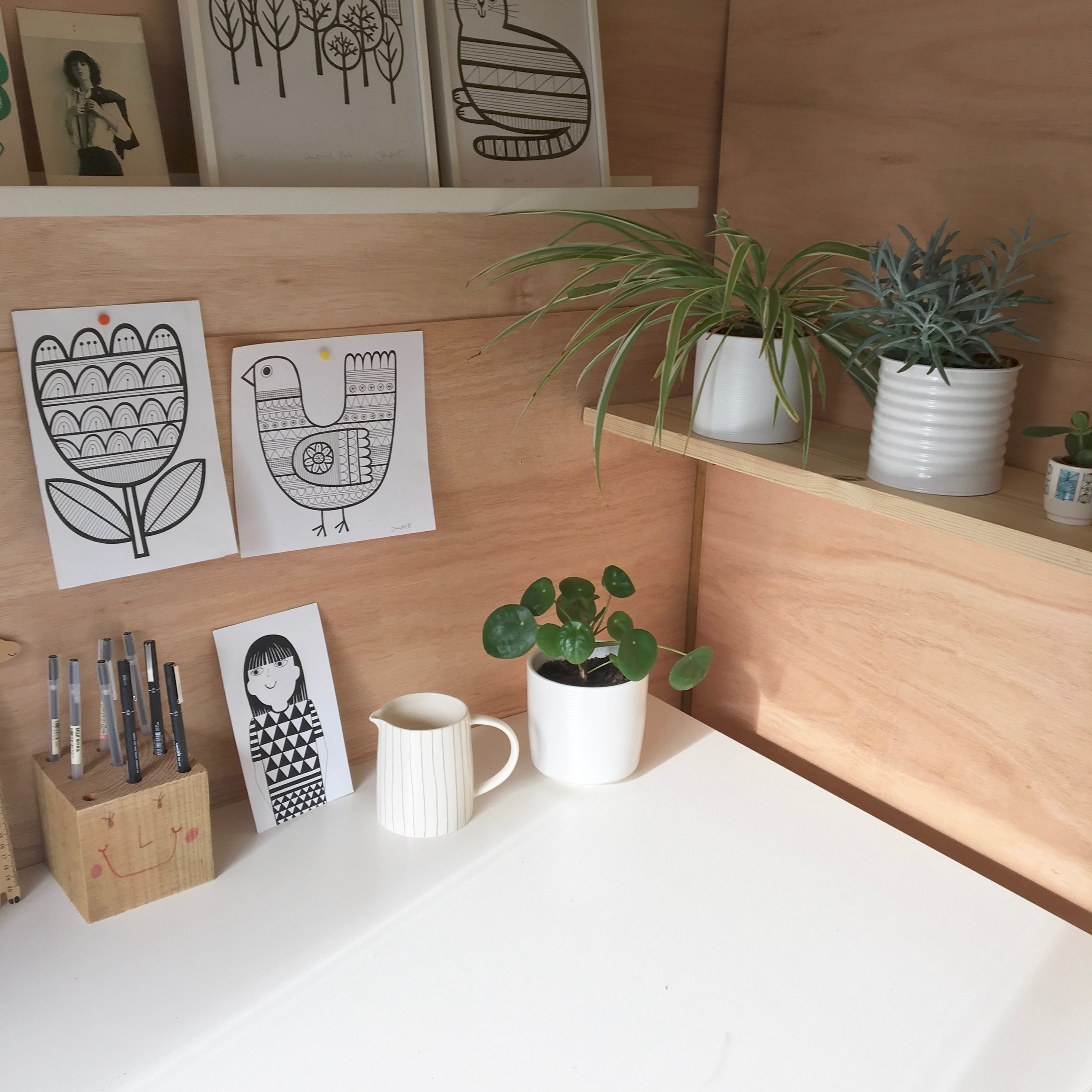 Some of my illustrations, my favourite pen holder made by my daughter and some plants. The striped jug is made by Rachel Barker.