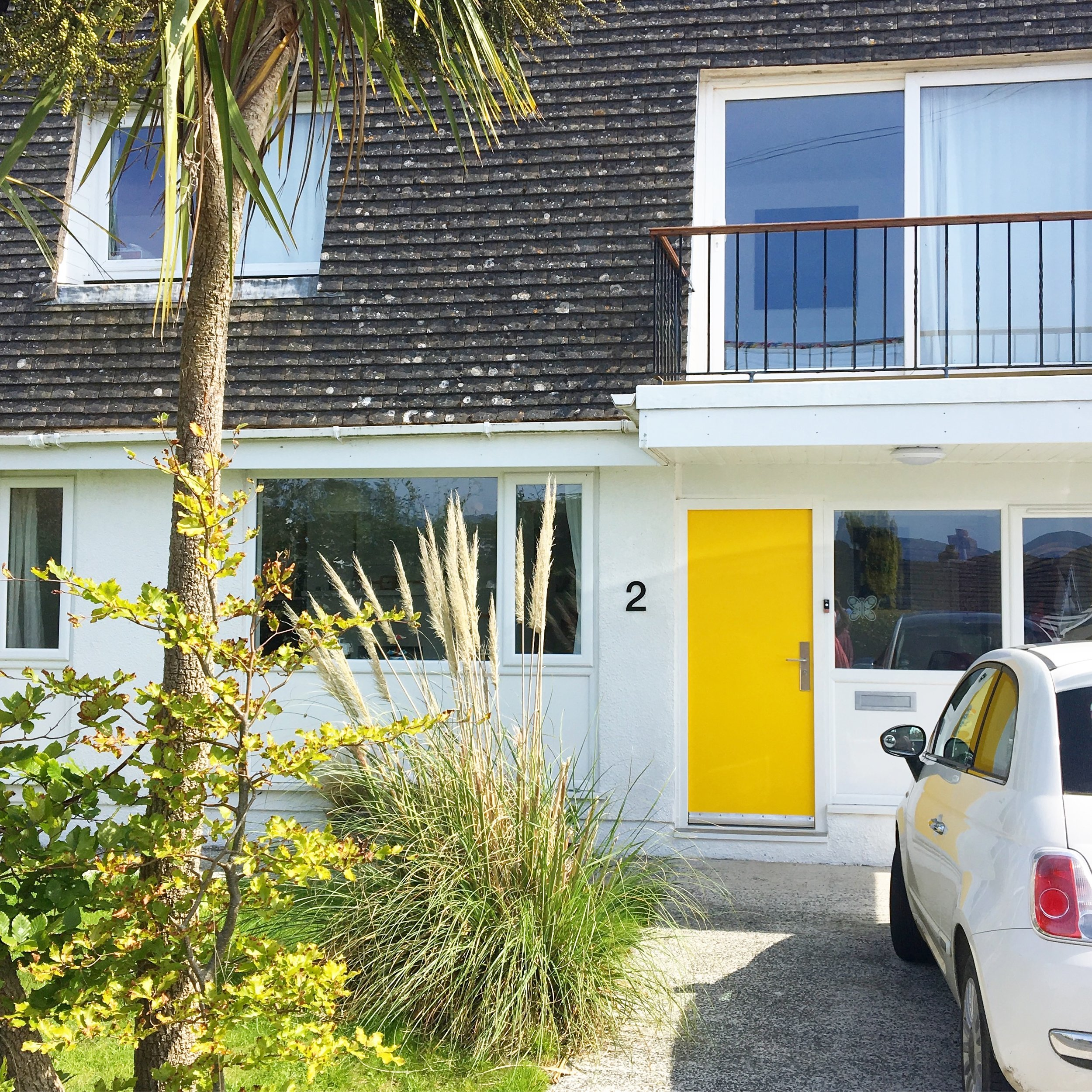 Our 60s home with it's new yellow door