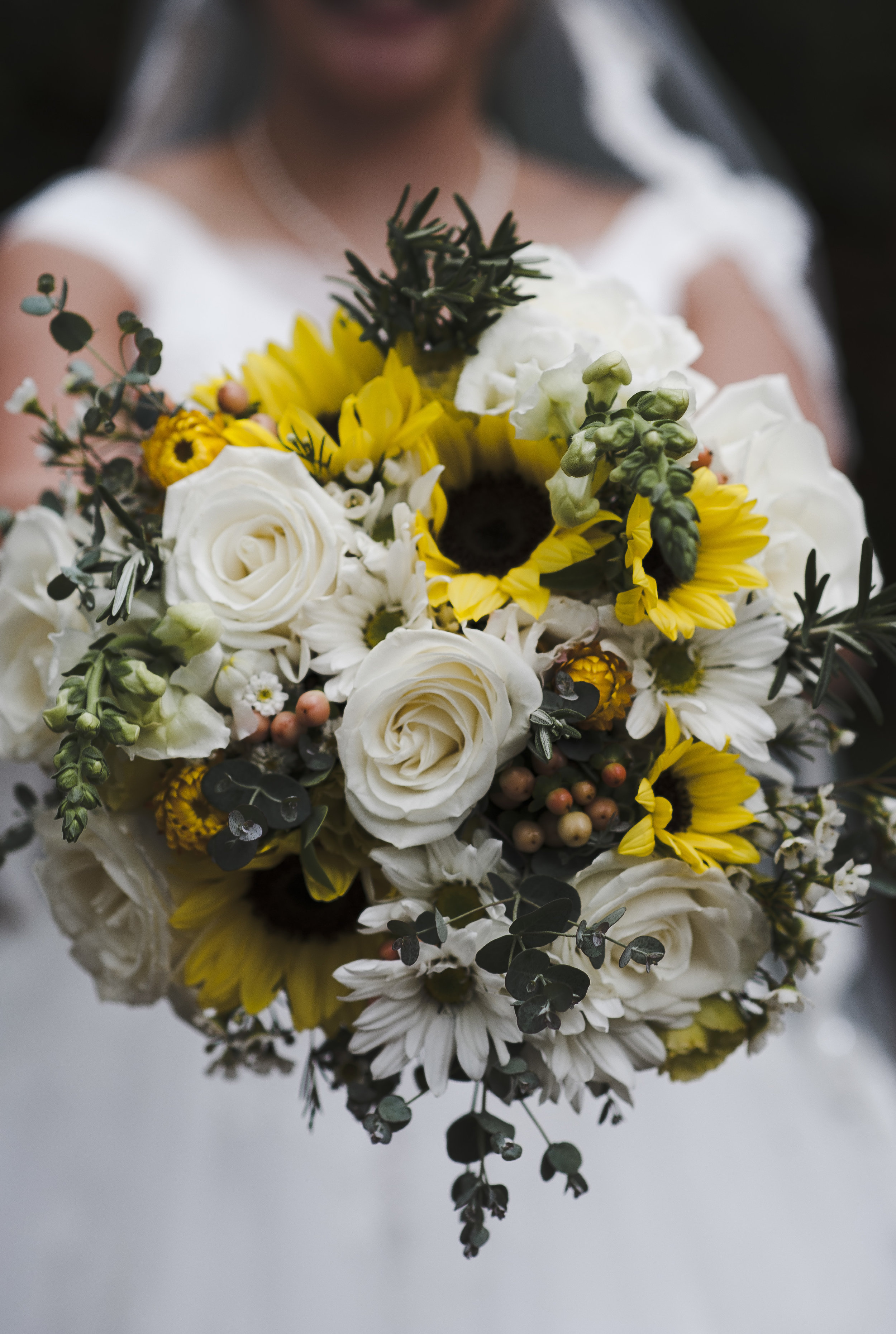 Sunflowers, snapdragons, the whitest roses, waxflower, and eucalyptus and rosemary to tie it altogether