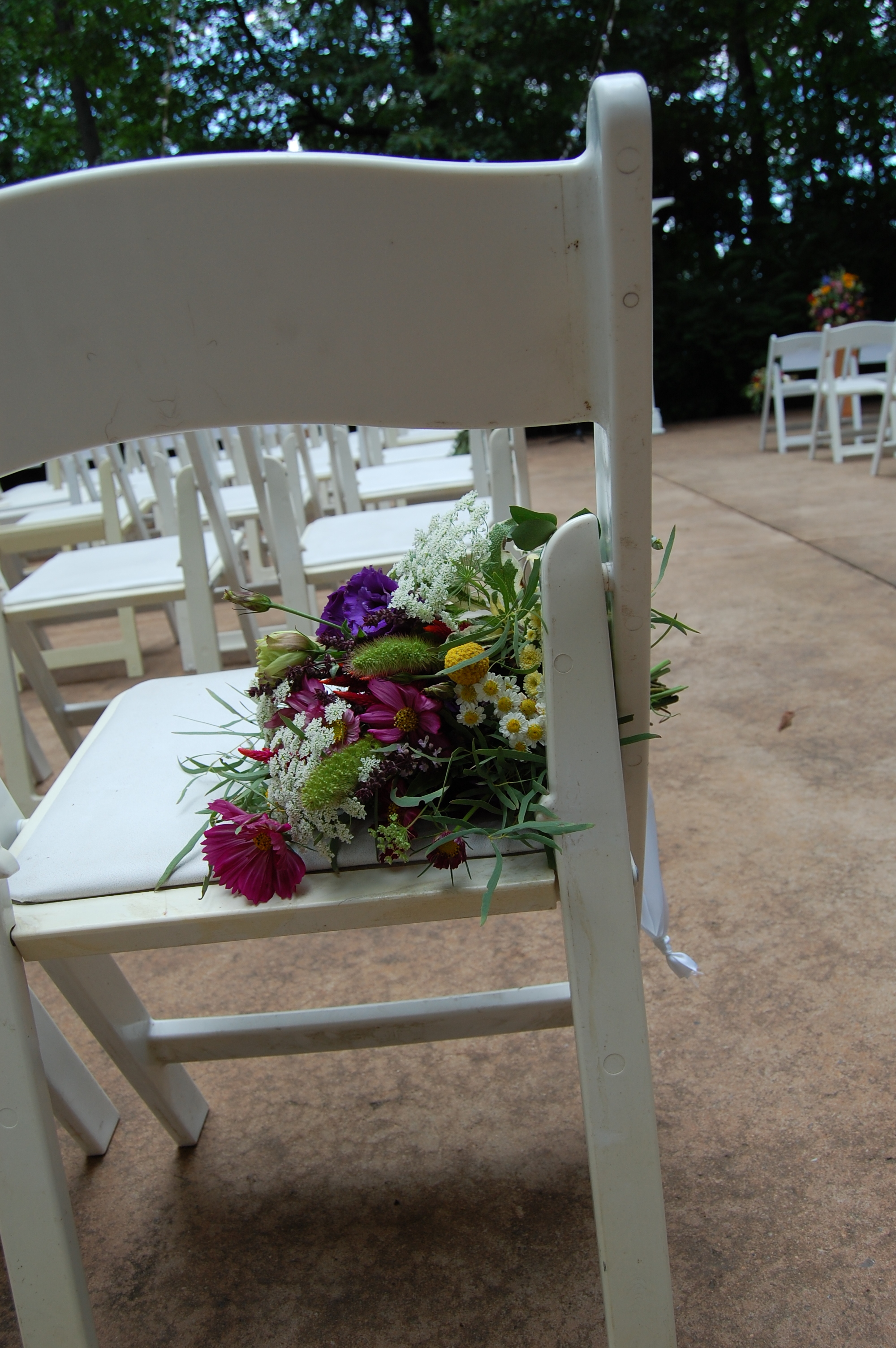 Wildflower bunches hung from the chairs bordering the aisle