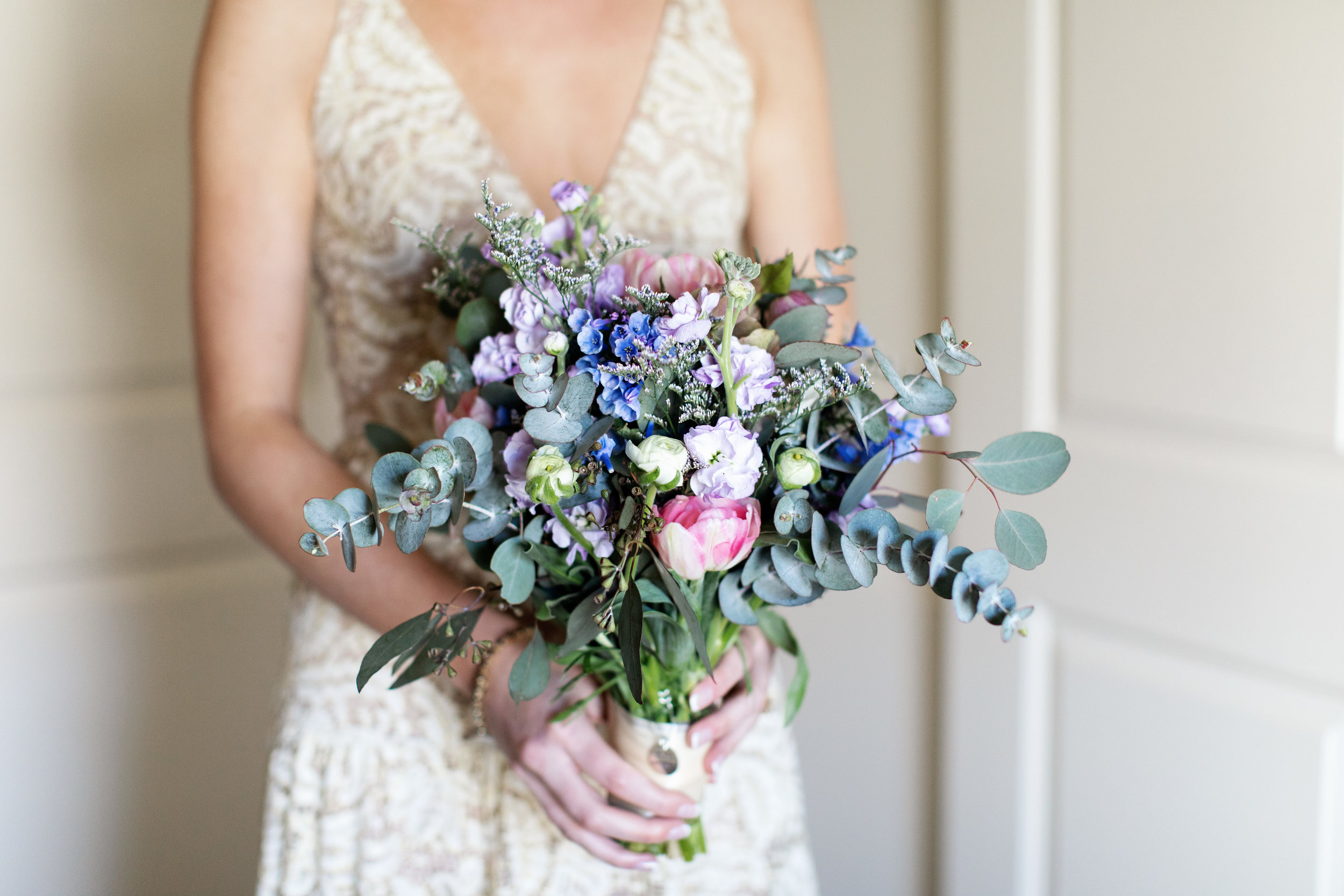 The Bouquet: Blush Angelique Tulips from the field complimented by sweet smelling lavender and white stock and blue delphinium. Eucalyptus is almost a given in bridal bouquets these days and it pulls this one together elegantly with muted gray greens.