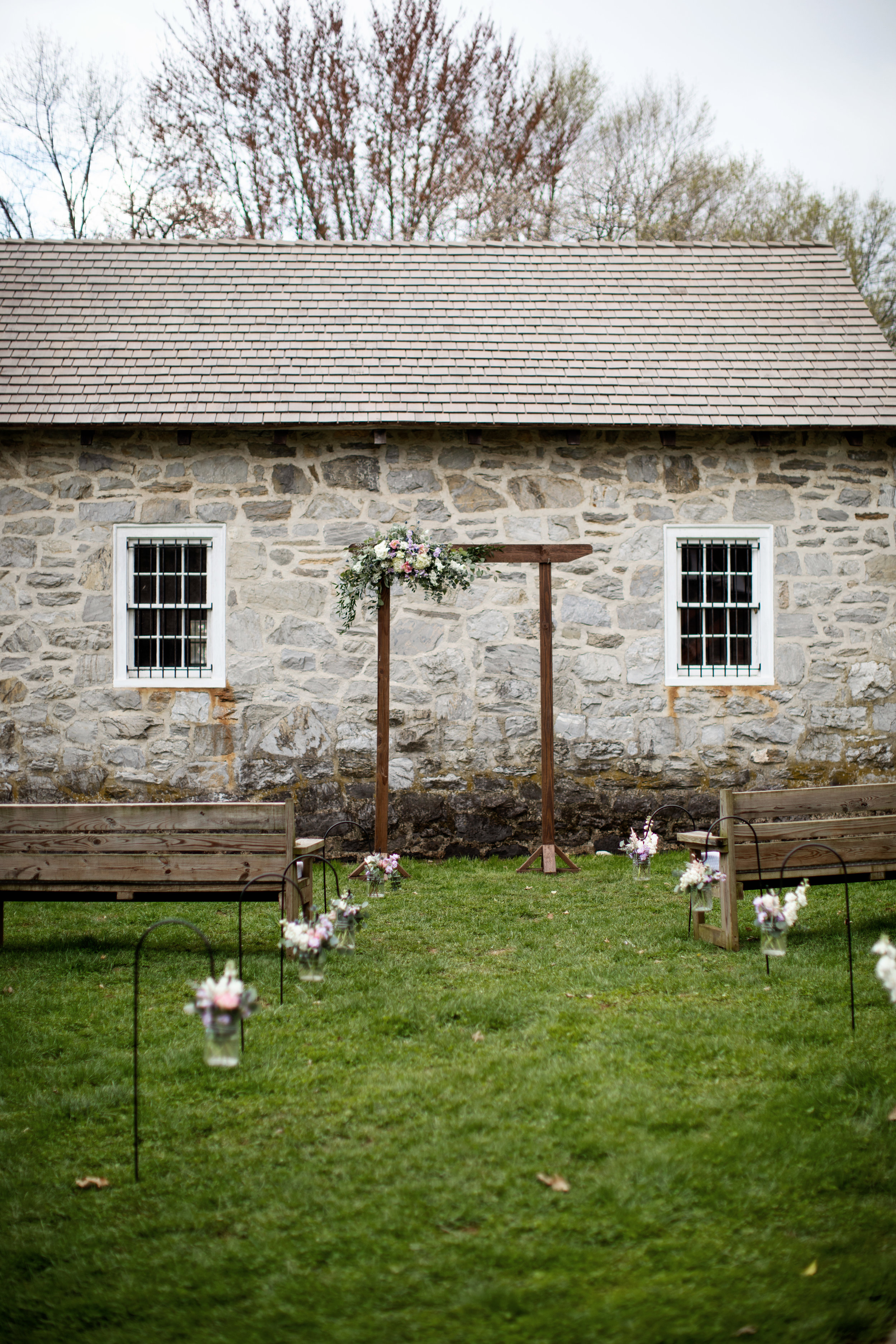 Ceremony flowers don't have to be huge and elaborate, an offset arbor spray and shepherds hooks bring just the right touch of color to frame an already beautiful setting.