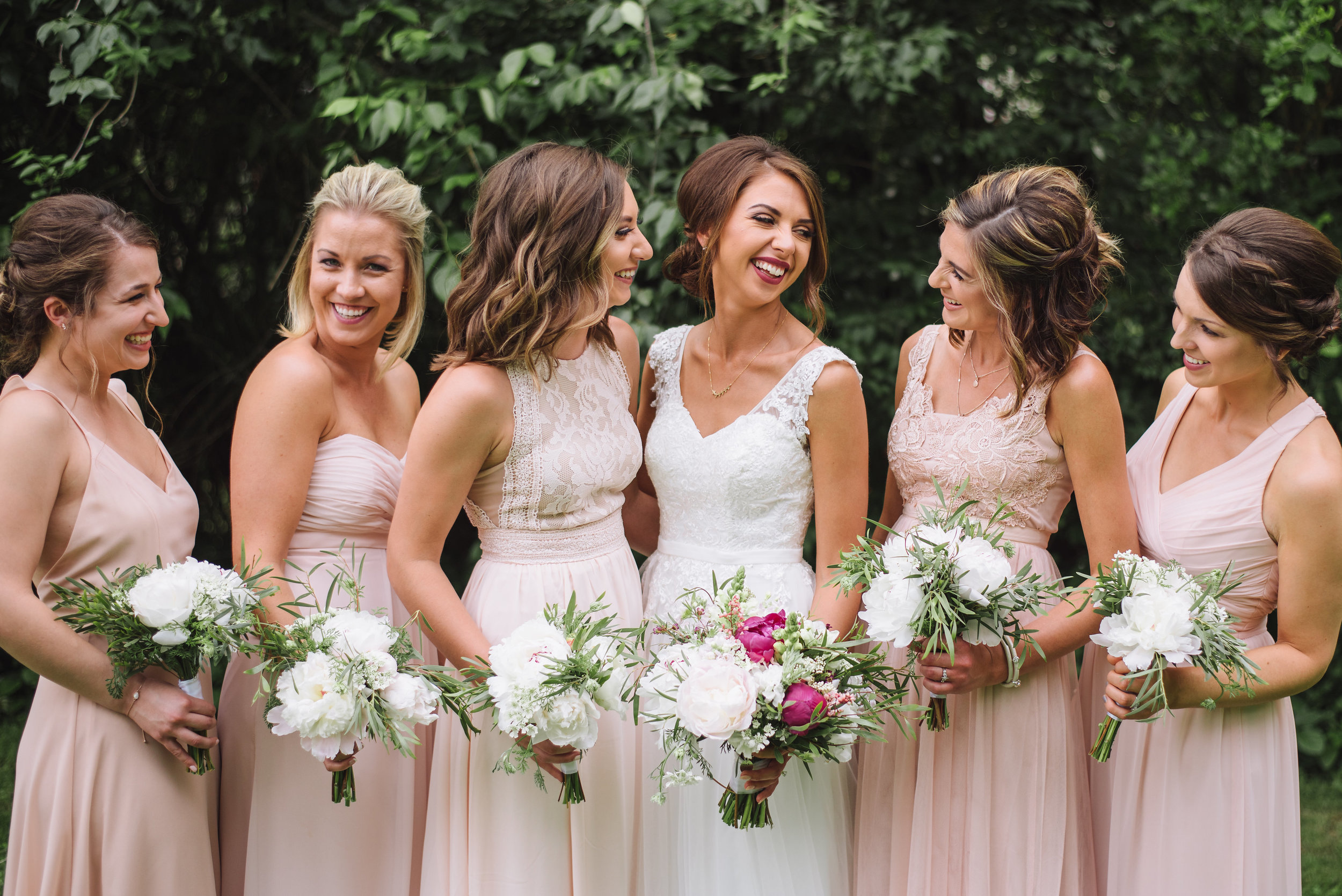 Adding pops of color to the brides bouquet while keeping the bridesmaid's white and green is a great way to let the bride stand out.