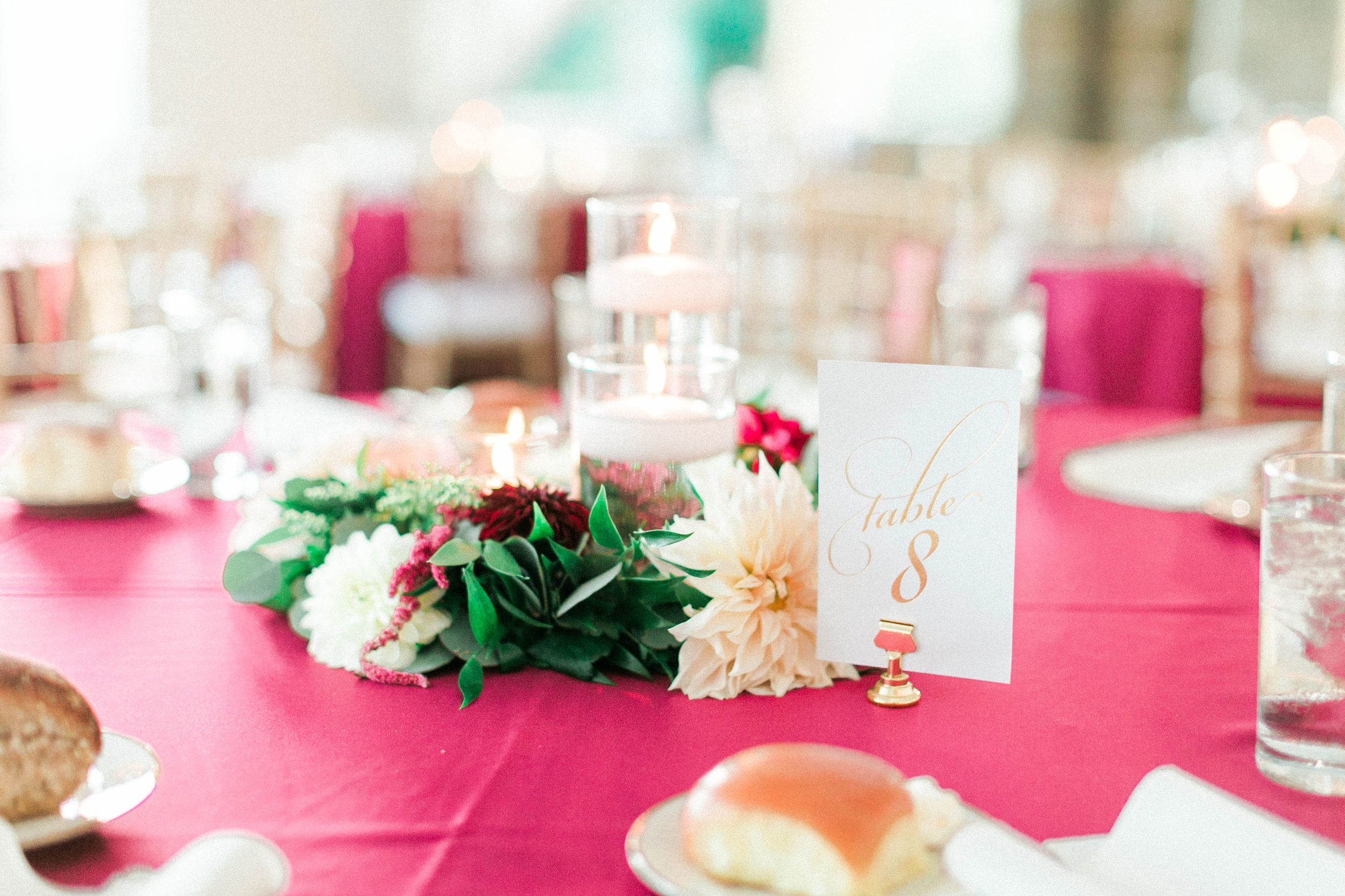 Another trend for centerpieces lately: These are thing garlands circling three pillar or floating candles. This adds color and life to the table without blocking anyone's view.