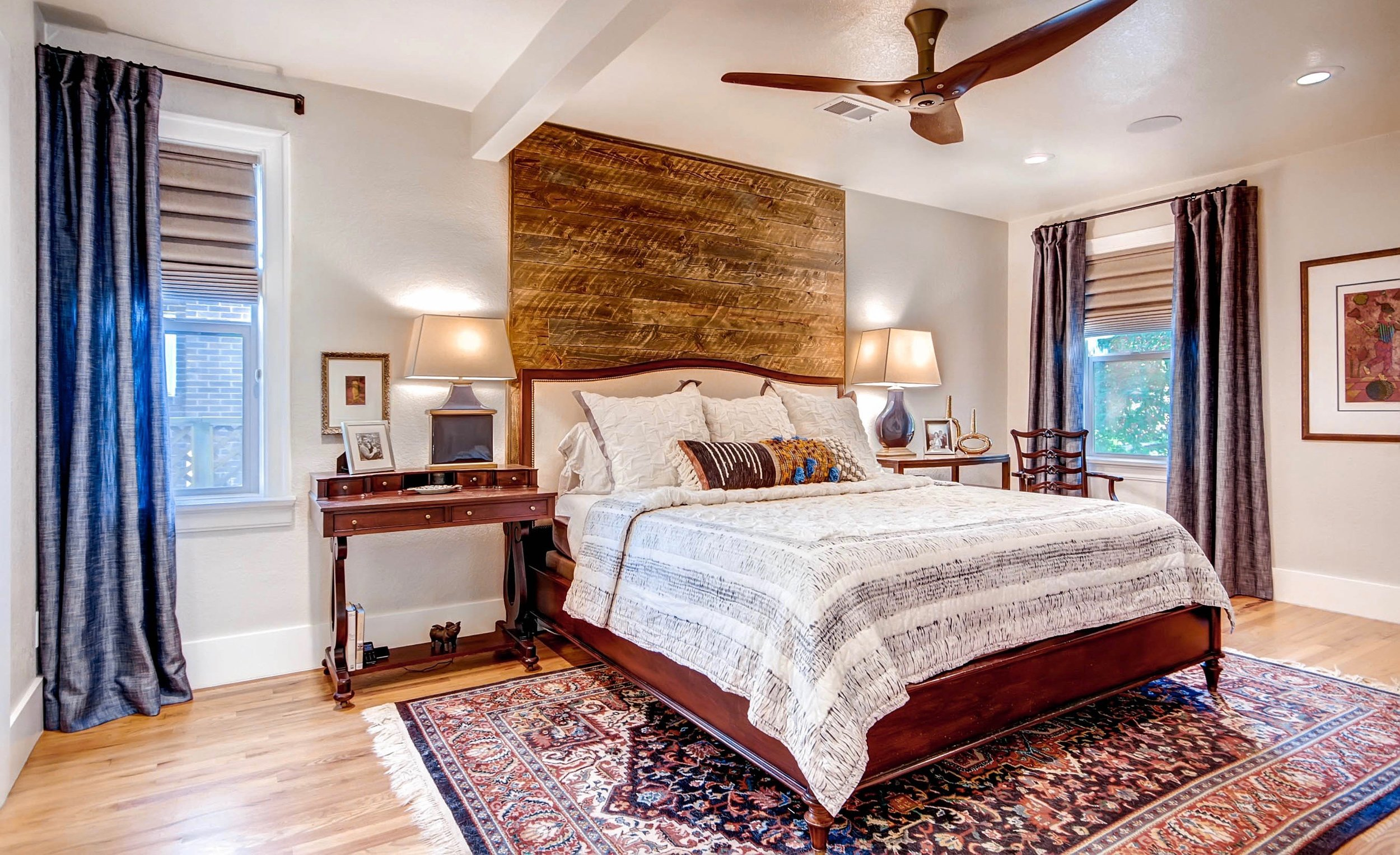 """A reclaimed, rustic-wood accent wall has dual purpose in this master bedroom -- it completely covers an unwanted window, and adds a chic focal point to the space. This is the """"Form Flirt Function"""" design approach in action."""