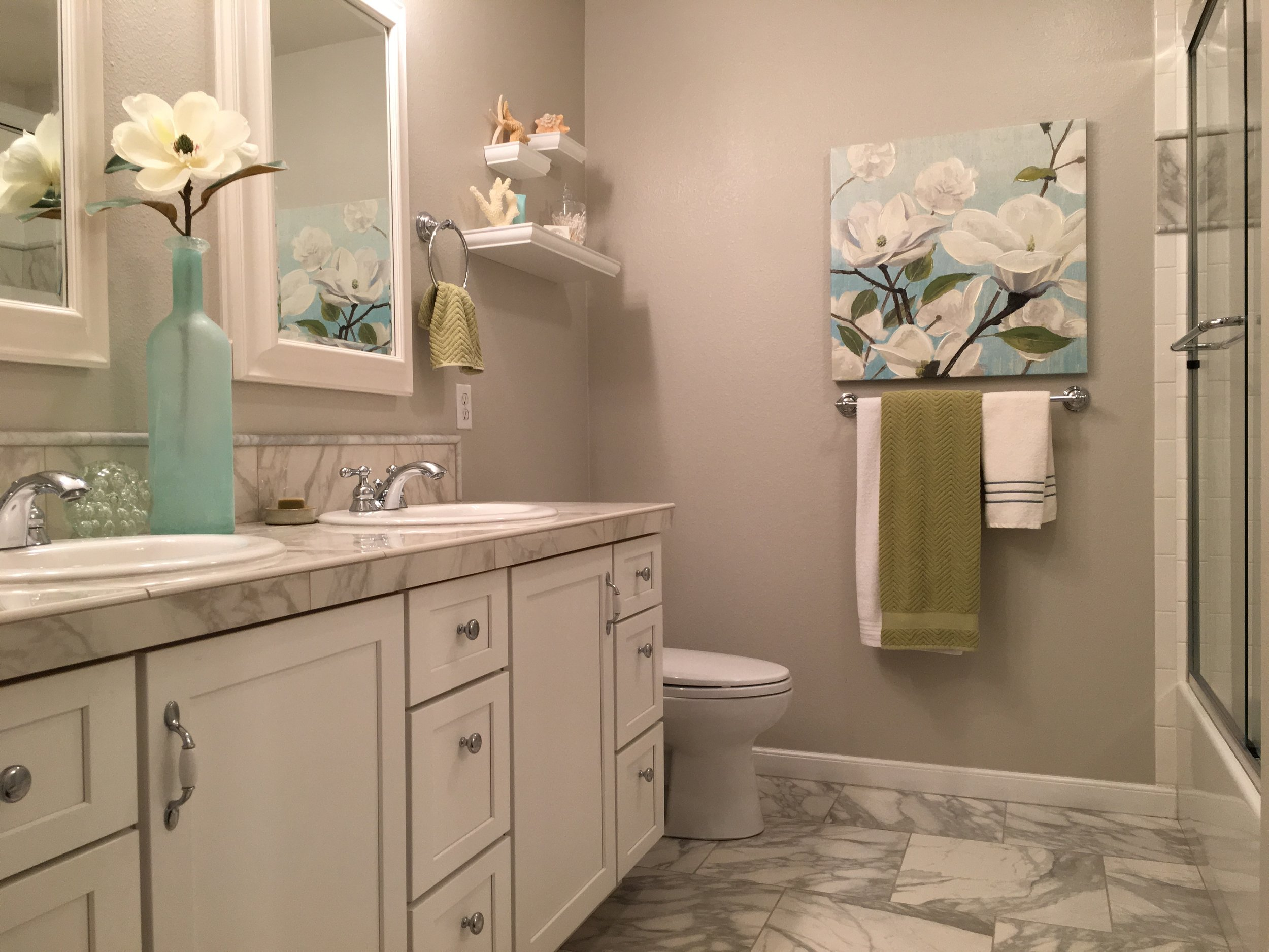 You can never go wrong with the classics -- a clean and fresh white/gray palette and a pop of color. White-painted shaker cabinetry combined with carrera marble tile accents will forever be in style.