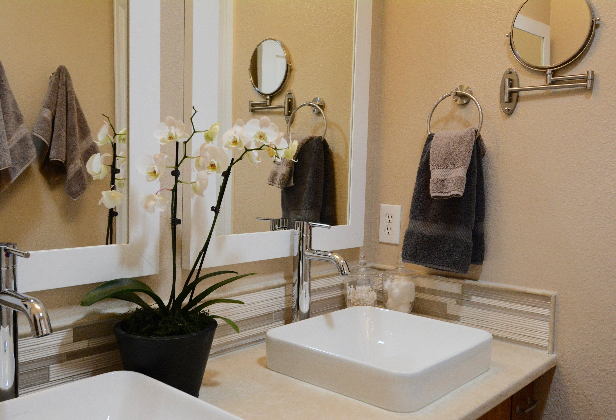This guest bath remodel was a total transformation. The new bamboo cabinetry, travertine countertops, stone and glass backsplash, modern sinks, and sleek faucets made this once childish space into a sophisticated and calming space.