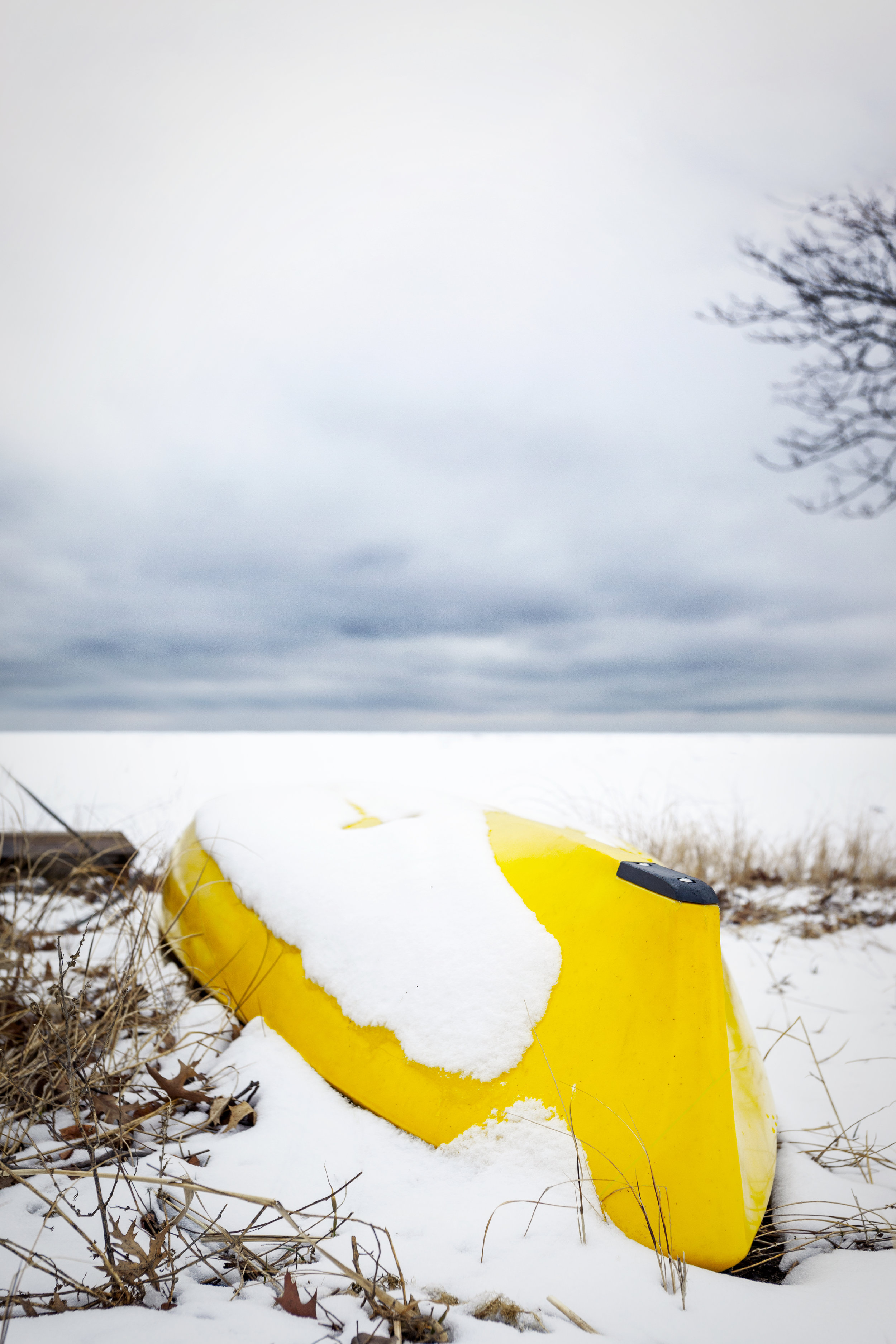 A yellow kayak upside down in the snow