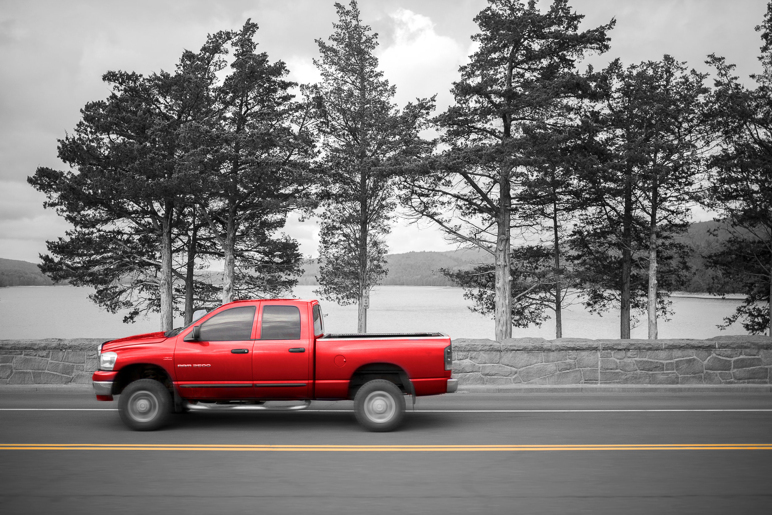 A red pick up truck near a lake
