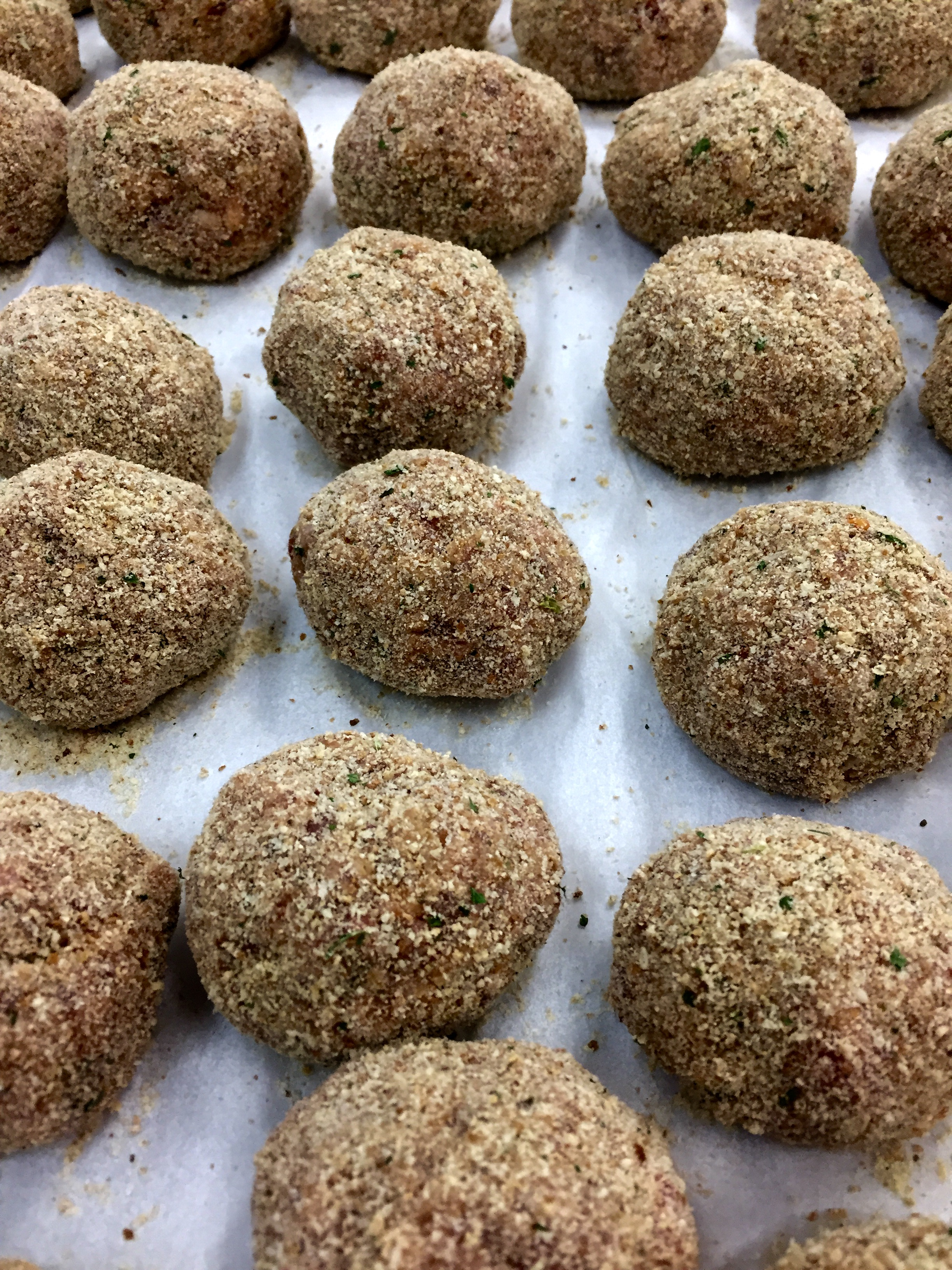 Hand-rolled meatballs breaded and ready to fry.