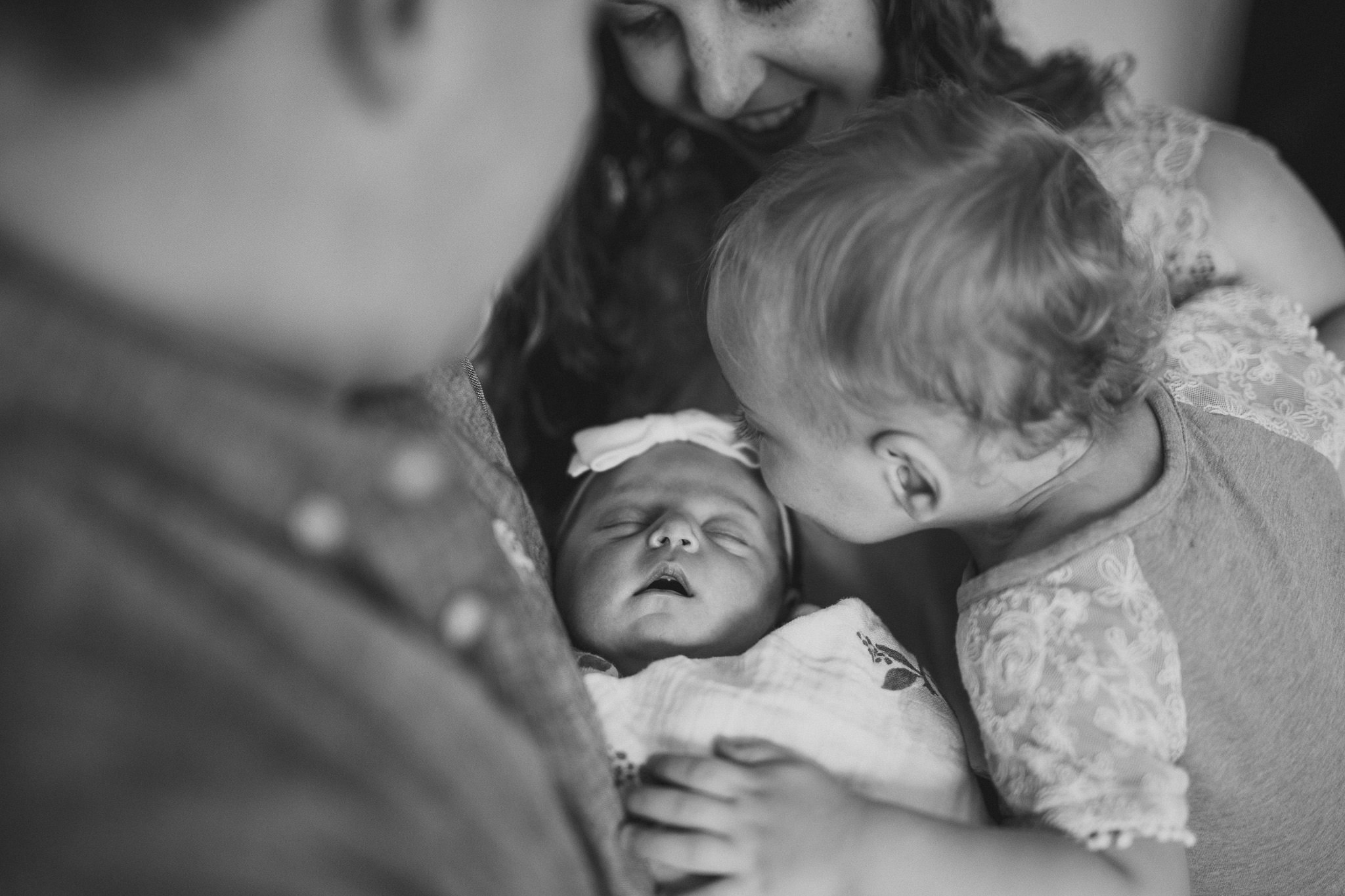 mom dad mother father looking at newborn baby holding in arms in home family nashville tennessee photography photographer photos session thomas wywrot black white