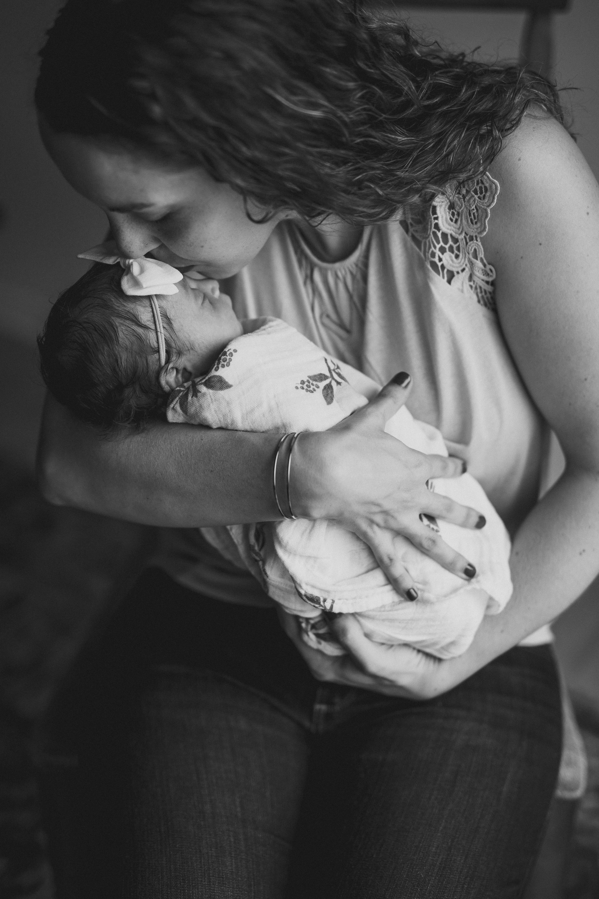 mother mom holding kissing newborn baby infant sitting love family session photos pictures thomas wywrot photography photographer nashville tennessee in home