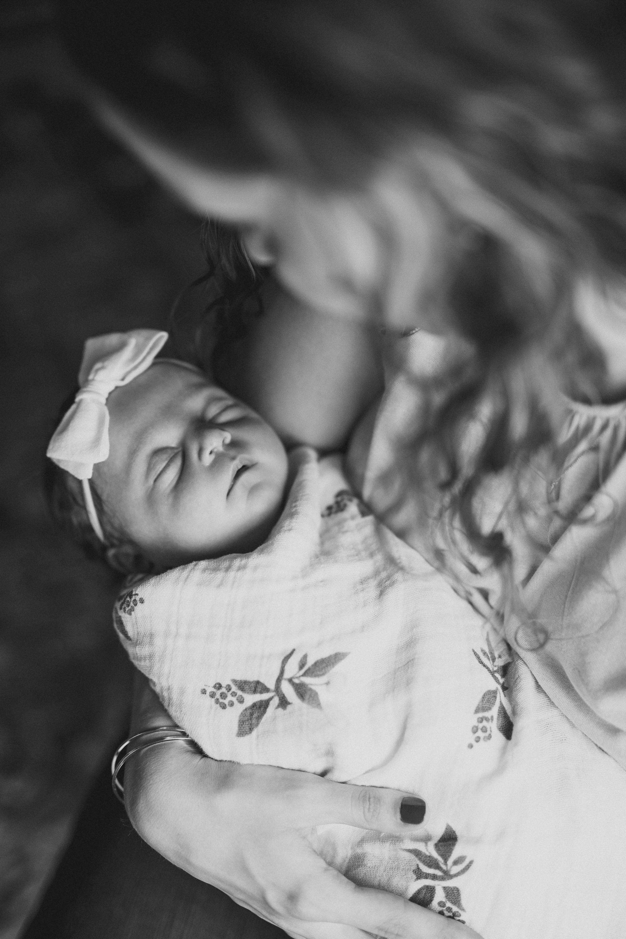 mom looking at newborn eyes closed held in arms in home newborn session nashville tennessee family photography photographer thomas wywrot tn