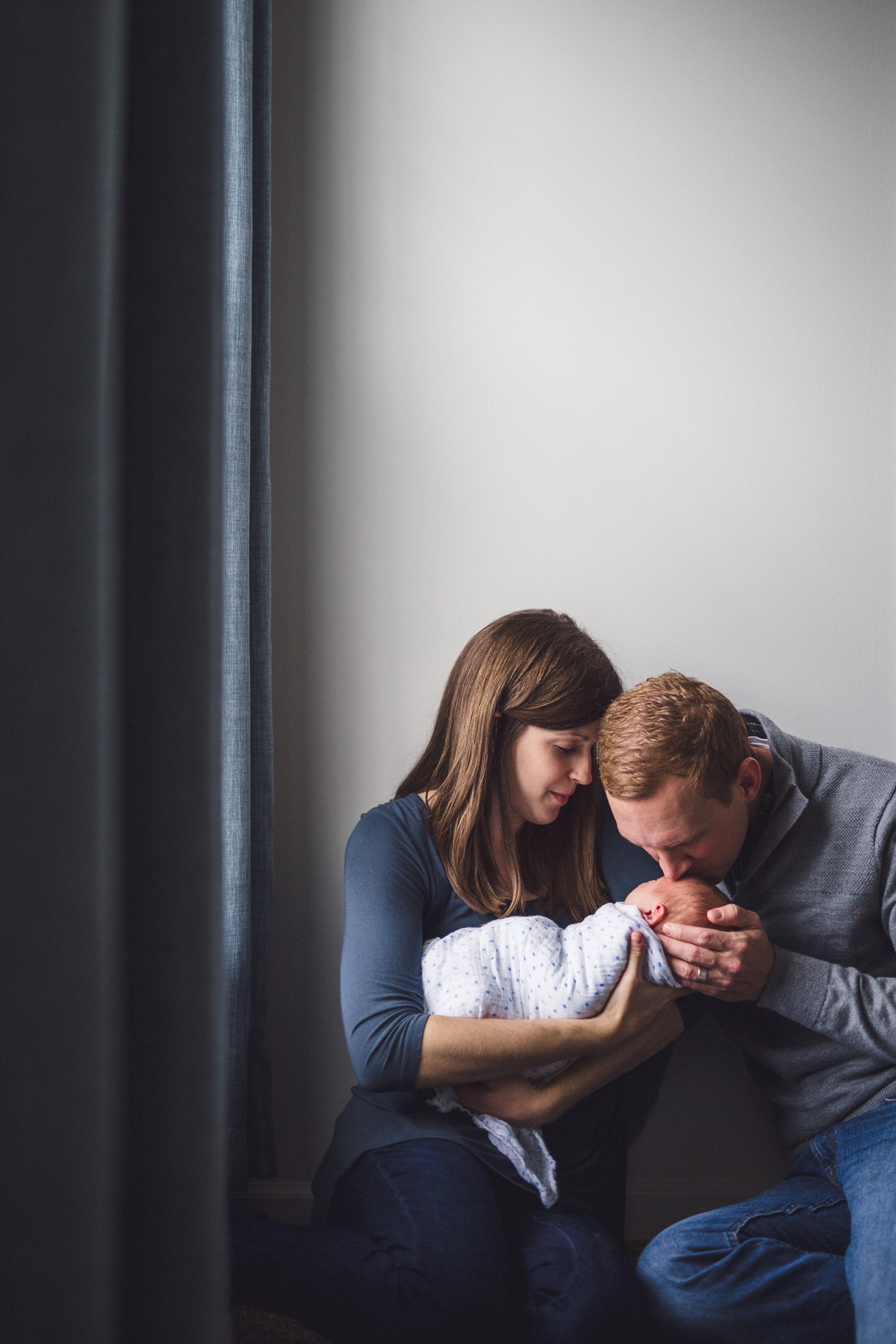 thomas wywrot photography nashville newborn photographer father kissing two week old baby on forehead while sitting with wife