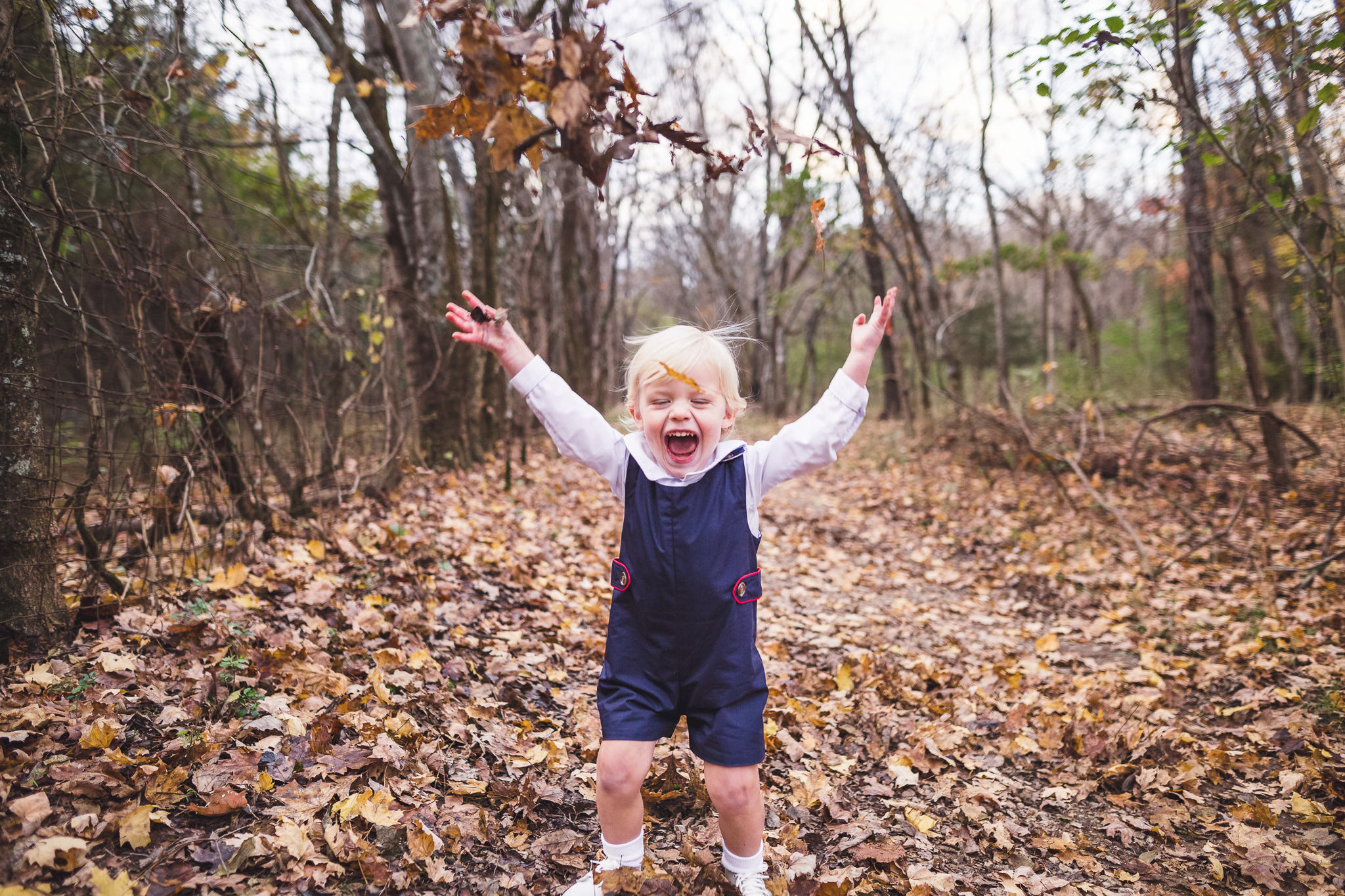 boy throwing leaves in the air fall family photos thomas wywrot photography nashville family photographer