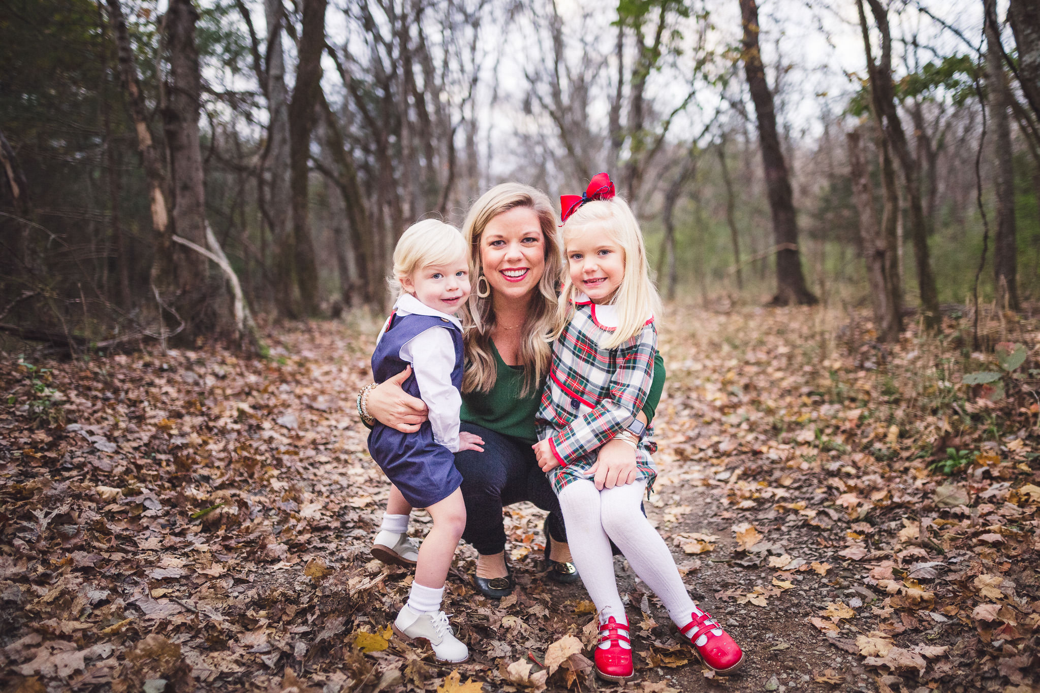 fall family photo outdoors with fallen leaves in forest thomas wywrot photography