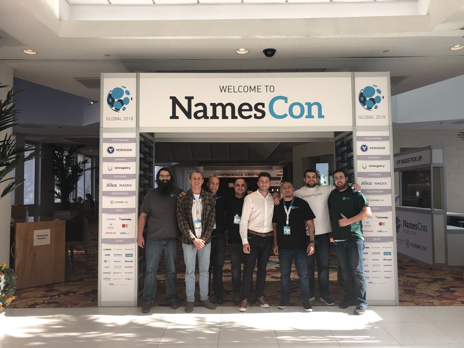 "Obligatory photo of the ""Emoji Experts"" and the  Domain Cost Club  team under the NamesCon welcome sign."