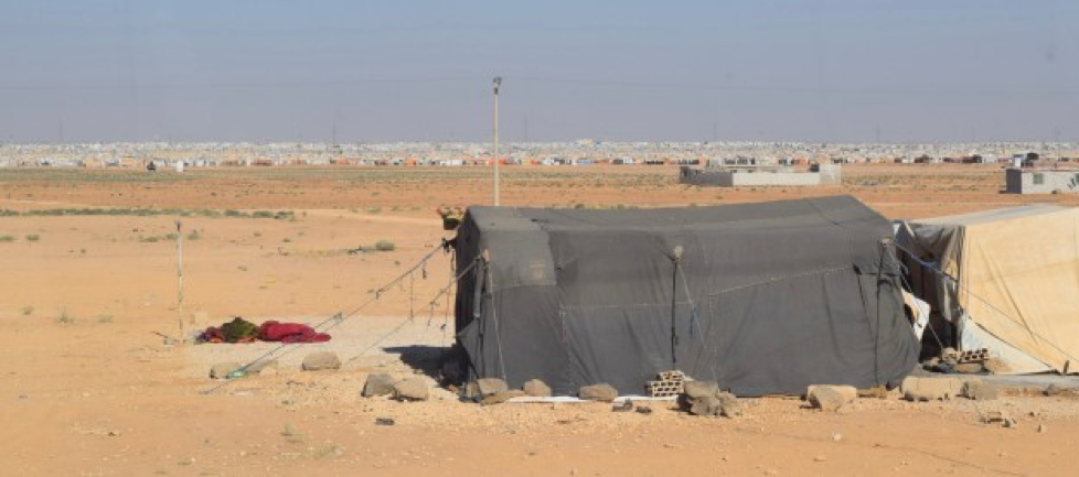 A modest tent shelter where a family lives, with the expansive spread of Zaatari seen in the background.