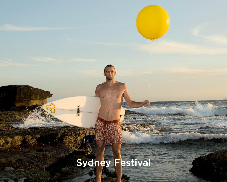 Man holding a yellow ballon & a surfboard on the beach