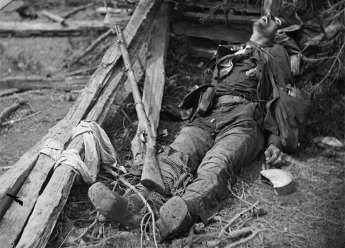 Dead soldier of Ramseur's Brigade with Enfield rifle and appears to wear a dark jacket. Note the various pieces of Federal accoutrements. Also visible is an uncovered Federal smoothside canteen. His cartridge box appears to be worn on his belt. ( LOC#: LC-B811- 723 )