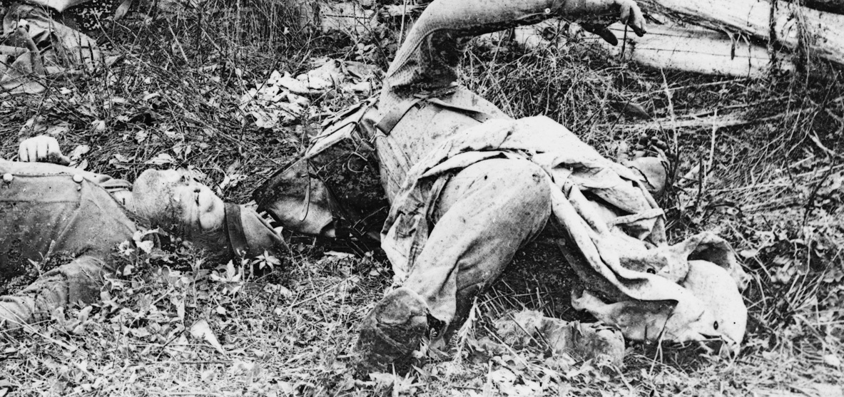 Dead Confederates along the Hagerstown Pike, one with a hard-pack knapsack. Notice the hole in the knee of his trousers, as well as the poor condition of his visible shoe. There appears to be a cap with a band in the image as well.