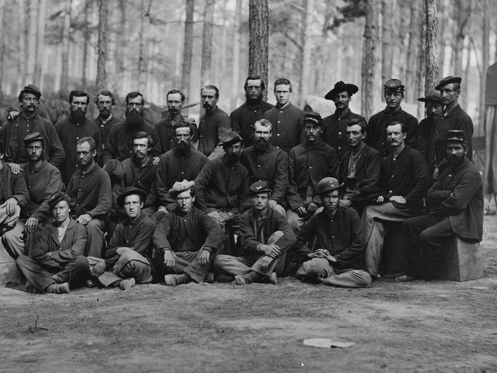 """August, 1864  """"Essayons Dramatic Club,"""" a group of the U.S. Engineer Battalion, near Petersburg, Va. Two men in this photo are wearing dark blues. (LOC#: LC-B817-7336)"""