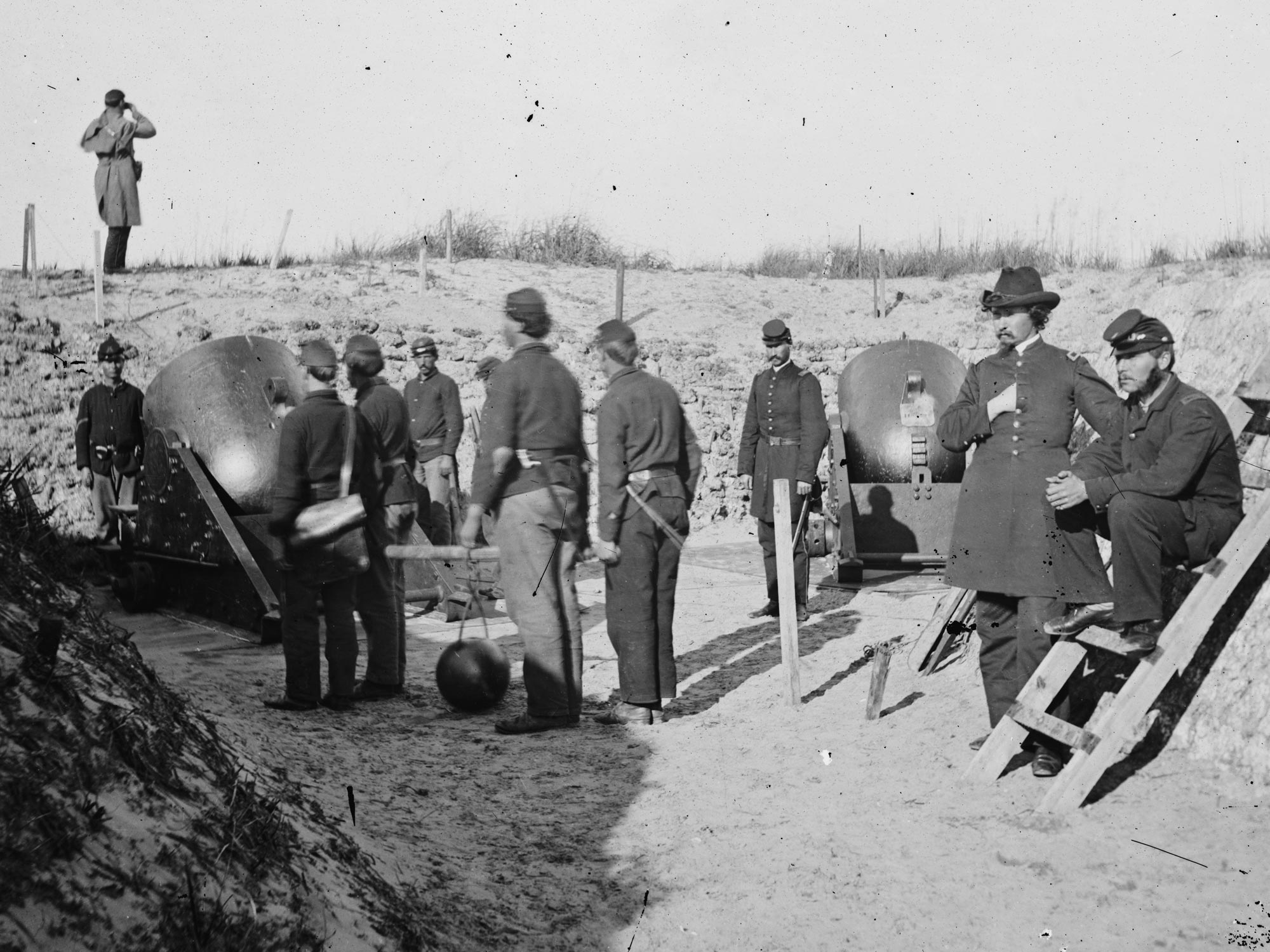 1865  An enlisted man in a mortar crew at Morris Island, SC opposing Ft. Sumter wears dark blue trousers. (LOC#: LC-B811-3513)