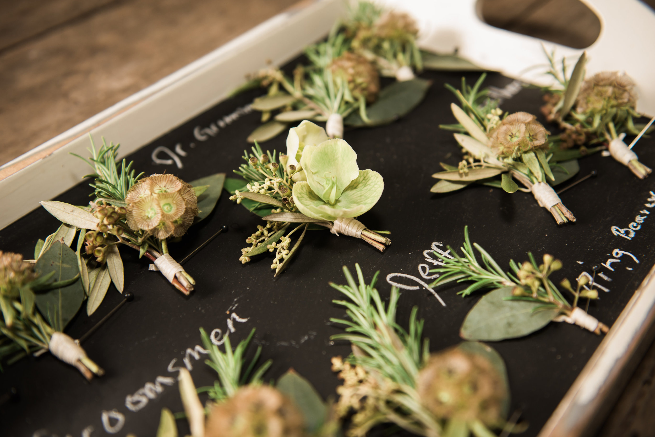 A Green and White Romantic Boho Wedding. Simple greenery boutonnieres with herbs, berries and helebores.   Flowers by Flower Buds   Photograph by Heart and Oak Photography   Venue The Ruins at Kellum Valley Farm