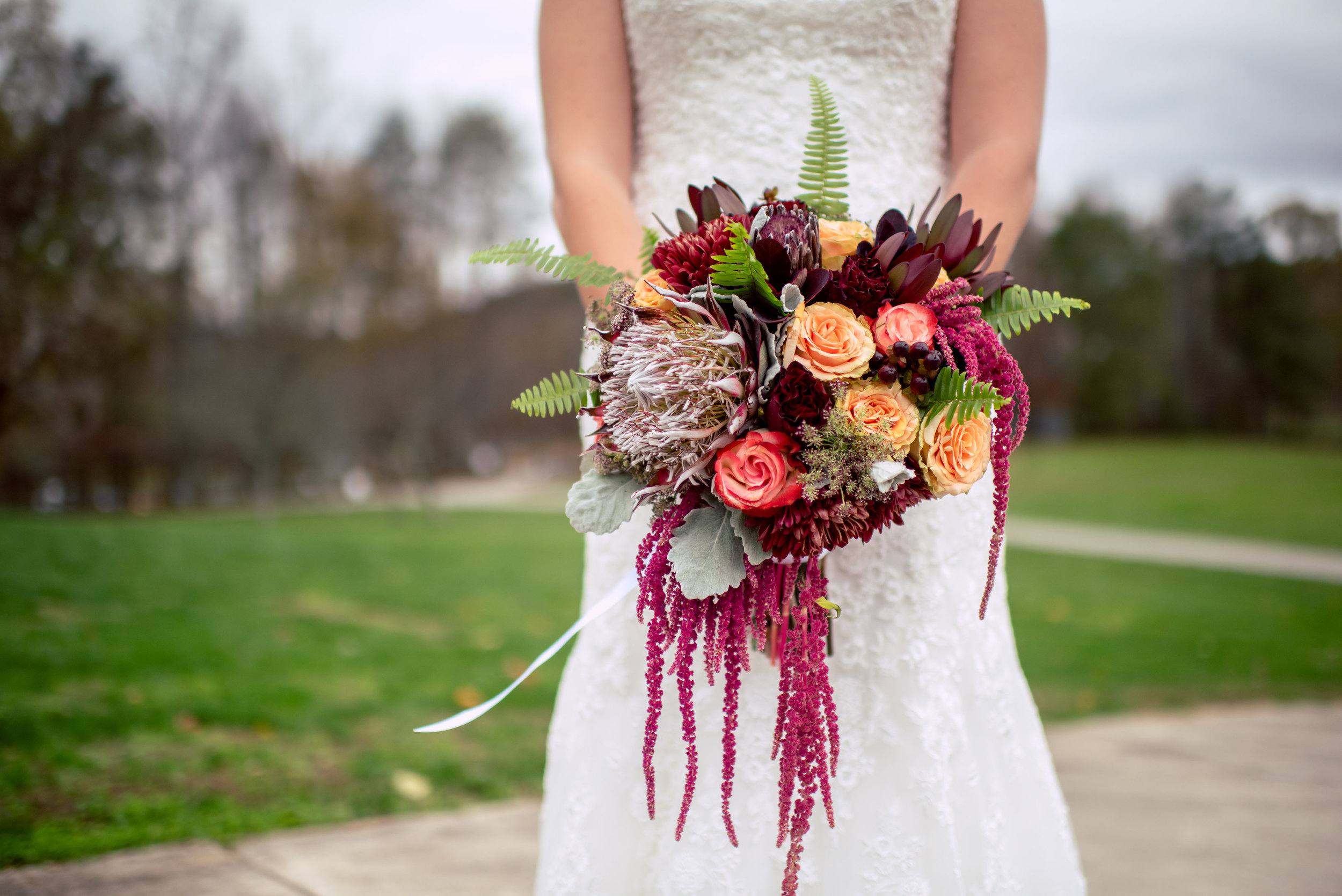 A Romantic, Jewel Toned Fall Wedding at The Ruins. Bridal Bouquet featuring jewel colored flowers including protea, leucadendron, roses, hypericum berries, hanging amaranthus and fern.| Flowers by Flower Buds. Picture by Once Like a Spark Photography. Venue The Ruins at Kellum Valley Farm