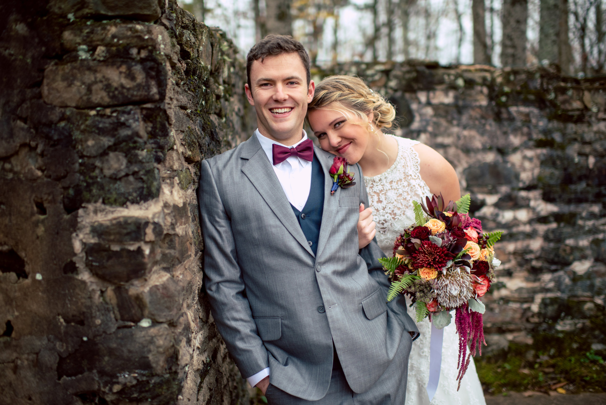 A Romantic, Jewel Toned Fall Wedding at The Ruins. Bridal Bouquet featuring jewel colored flowers including protea, leucadendron, roses, hypericum berries, hanging amaranthus and fern.  Flowers by Flower Buds. Picture by Once Like a Spark Photography. Venue The Ruins at Kellum Valley Farm