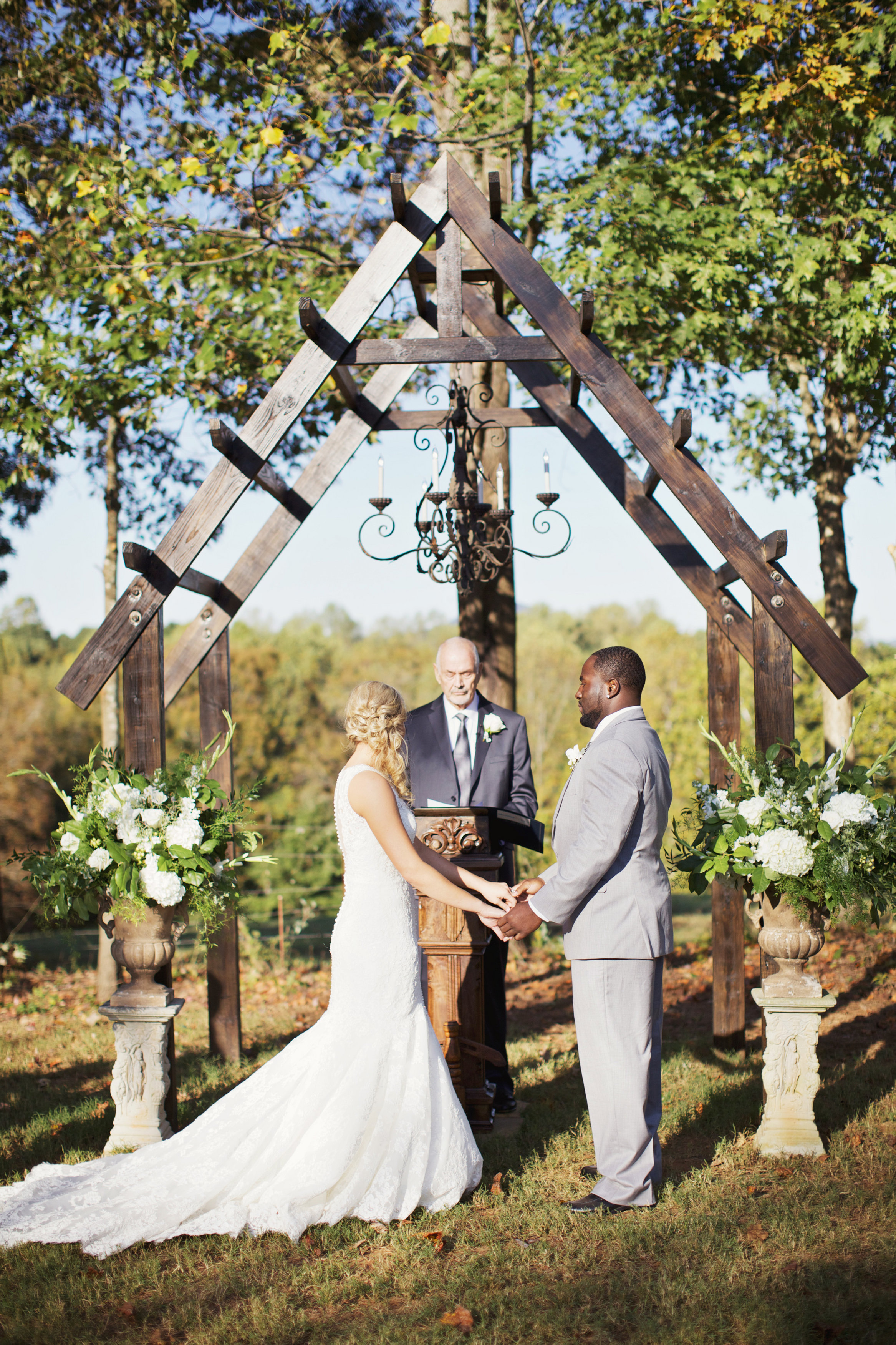 An Intimate Backyard Wedding featuring Traditional Wedding Florals. Ceremony Arrangements of White Flowers and Greenery.   Flowers by Flower Buds. Picture by Happy Everything Co.