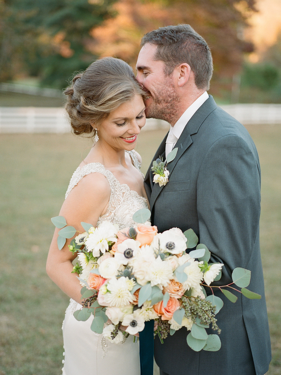 Peaches and Cream Bridal Bouquet featuring white anemones, peach roses, white ranunculus, white dahlias, privet berry and silver dollar eucalyptus.   Flowers by Flower Buds. Photo by Davy Whitener Photography. Venue The Ruins at Kellum Valley Farm