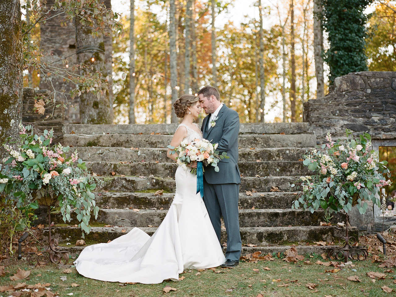 A Romantic Peaches and Cream Outdoor Wedding at the Ruins featuring white anemones, peach roses, white ranunculus, white dahlias, privet berry and silver dollar eucalyptus.   Flowers by Flower Buds. Photo by Davy Whitener Photography. Venue The Ruins at Kellum Valley Farm