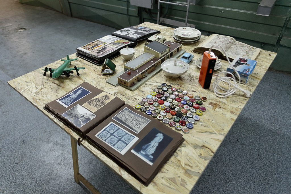 The objects on the table included many soda caps, old photo albums of travels, an old map book, ceramic bowls, an old cassette player, a model of a building complex and toys of a plane and cars.