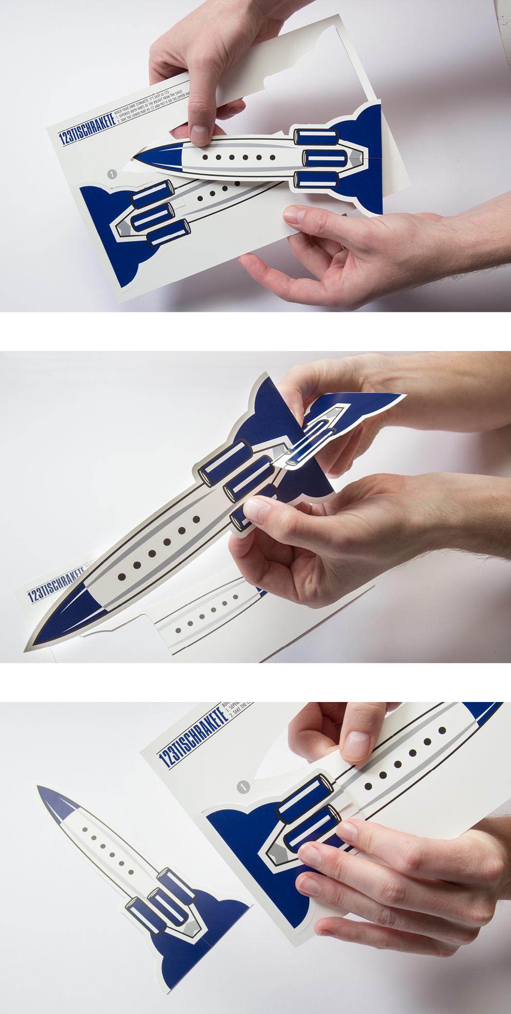 Bastelanleitung für blaue Rakete auf weißem Hintergrund für die 123Tischrakte. Mit Perforierung um aus der Rakete eine kleinen Raktenaufsteller zu bauen. Für die Party 123 Rakte von Red Bull gestaltet von den sons of panema, Grafikbüro in Köln.
