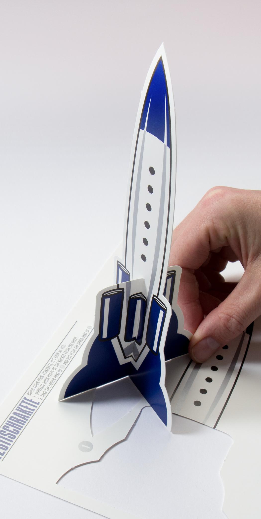 Bastelanleitung für blaue Rakete auf weißem Hintergrund für die 123Tischrakte. Mit Perforierung um aus der Rakete eine kleinen Raktenaufsteller zu bauen. Aufgestellte Rakete, für die Party 123 Rakte von Red Bull gestaltet von den sons of panema, Grafikbüro in Köln.