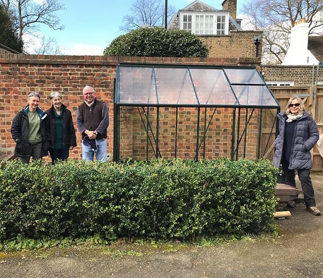 Bell House volunteers and newly built greenhouse