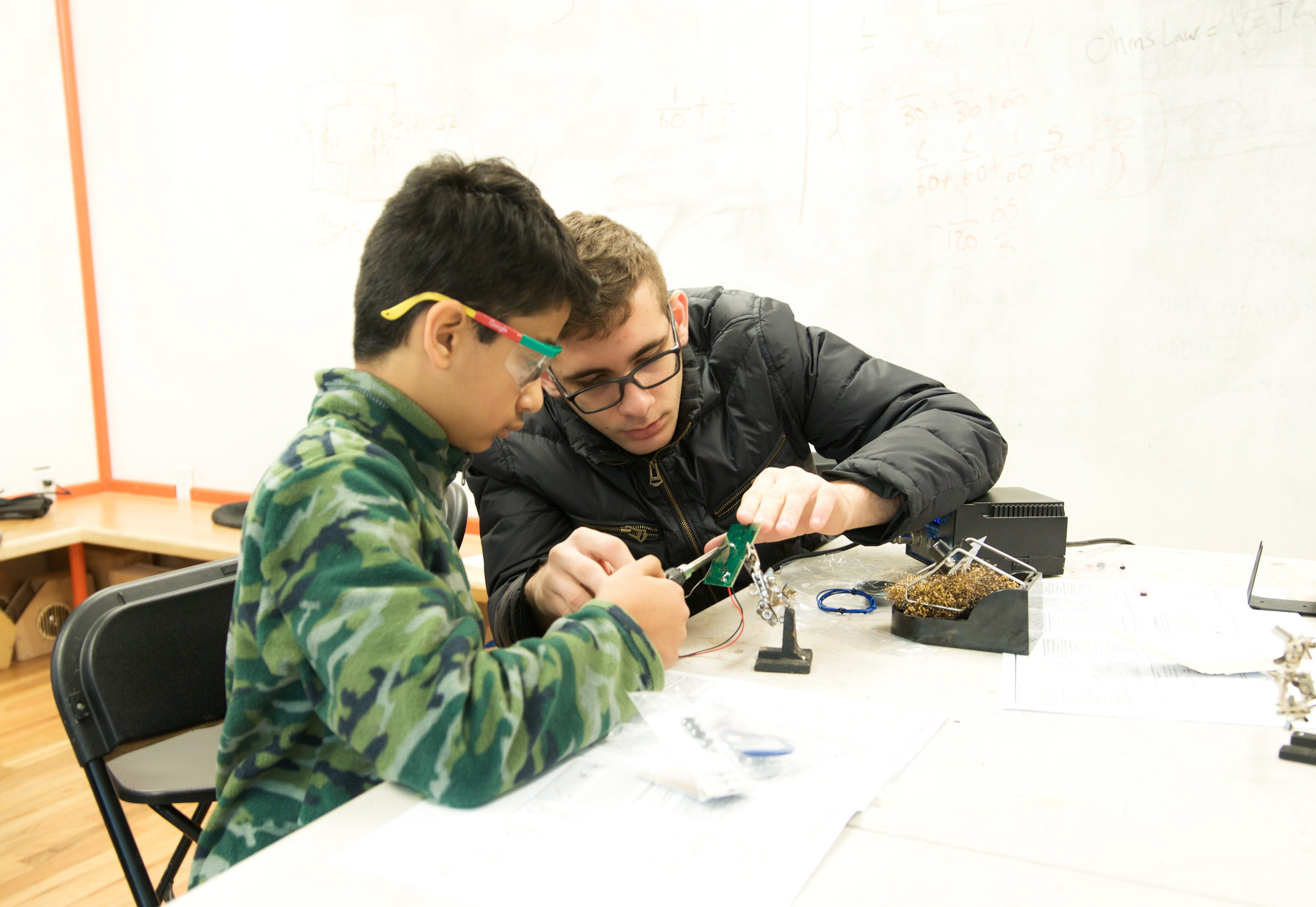 Mentor teaching student soldering on a circuitboard during program