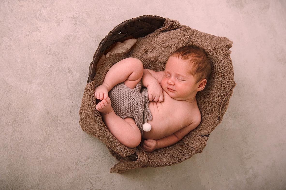 4 week old newborn in basket smiling.jpg
