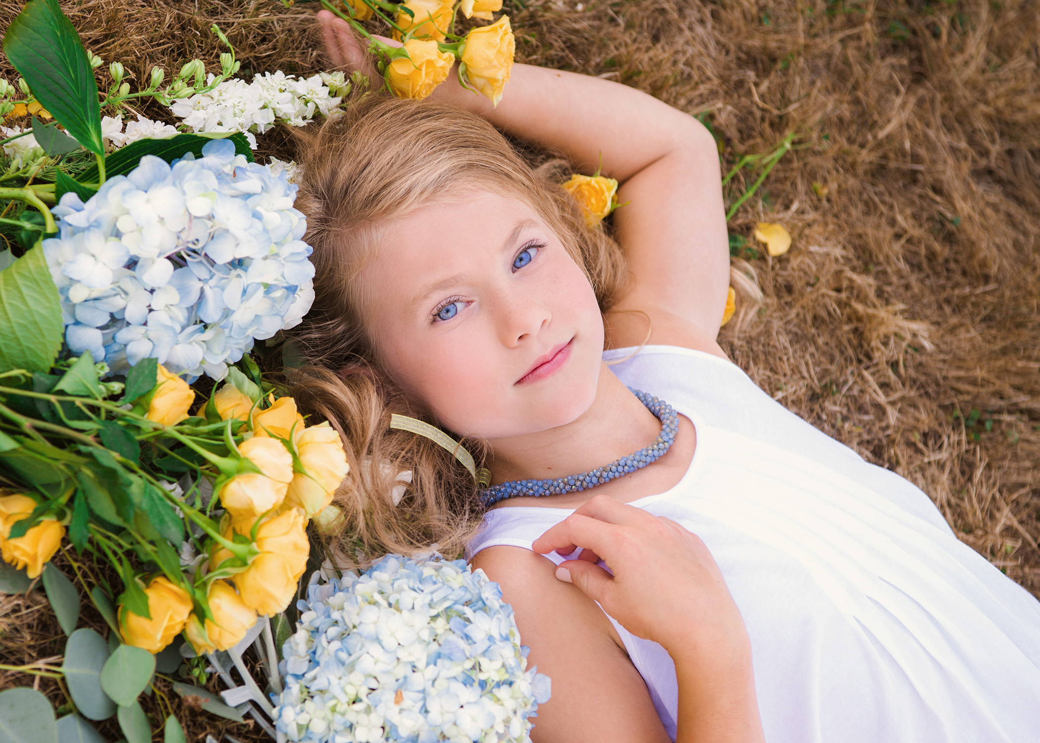 A bouquet of flowers is an easy way to add a well placed pop of color and feminity to your children's portraits
