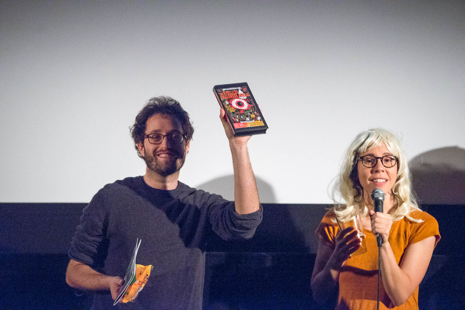 "Dan and Vanessa of The Eyeslicer showing one of the costume contest prizes, a VHS copy of ""The Eyeslicer Halloween Special"""