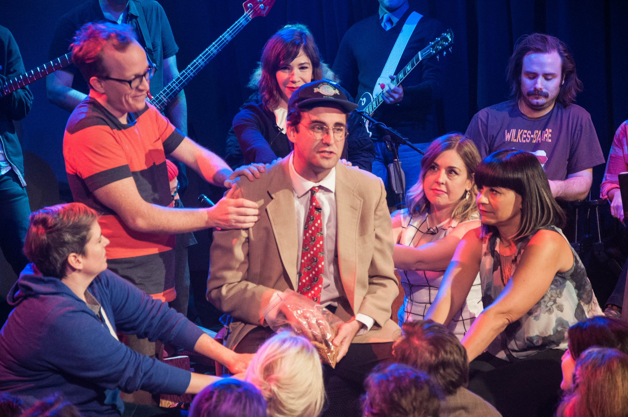 "People place their hands on the bad one (played by John Reynolds) during an episode of ""The Chris Gethard Show"" named after Sleater-Kinney's song. Members of S-K play along too (Carrie Brownstein in the background, Corin Tucker and Janet Weiss in the foreground on the right)."