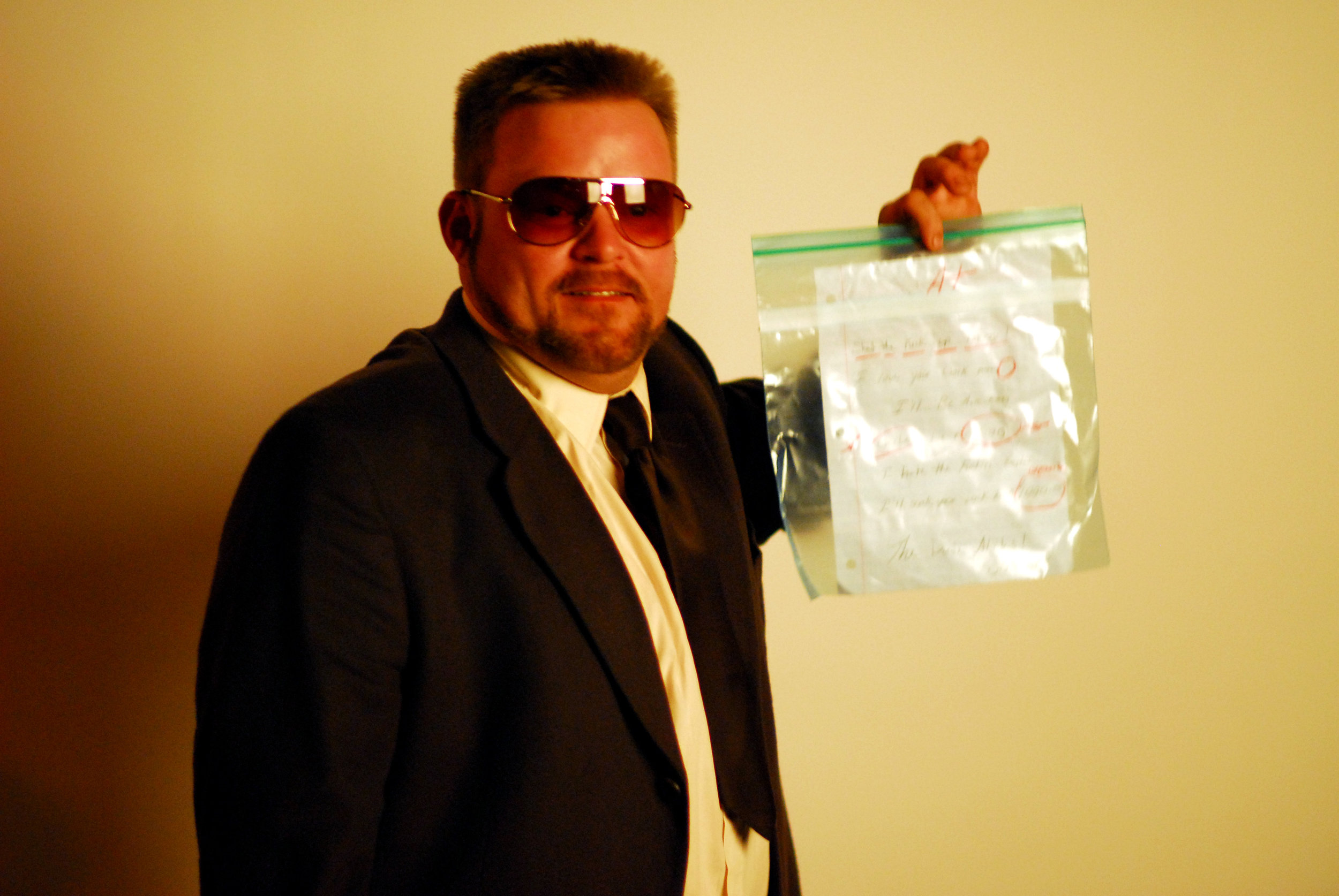 A participant in the NYC  Lebowskifest , dressed as John Goodman's character, holds up homework contained in a Ziploc bag on Sunday, November 16, 2008 at Lucky Strikes Lanes in New York, NY.