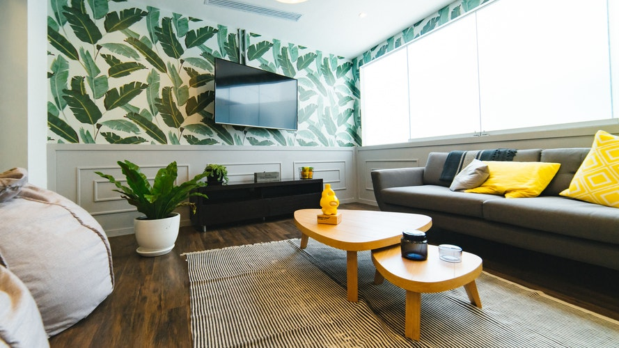 Bright modern living room with jungle themed wall paper.