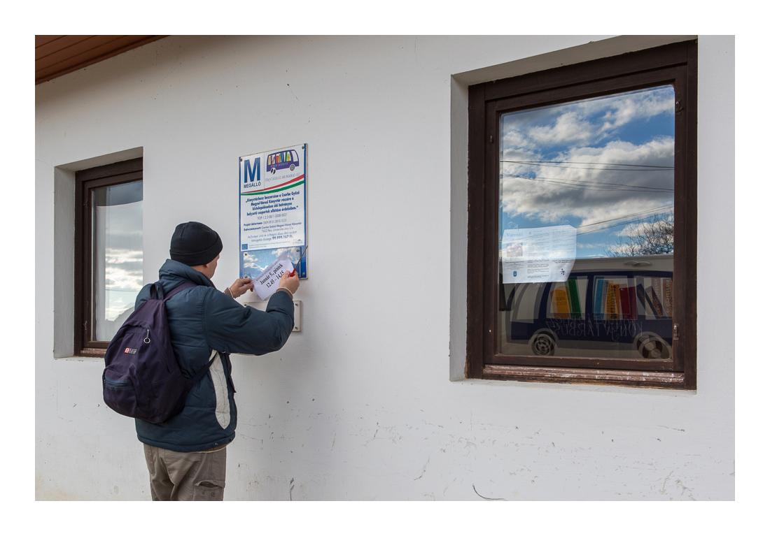 Menetrend. Gábor, a sofőr kihelyezi a következő látogatás időpontját a könyvtárbusz-megállóba, aztán irány a következő település. Lúzsok, 2017. 12. 08.