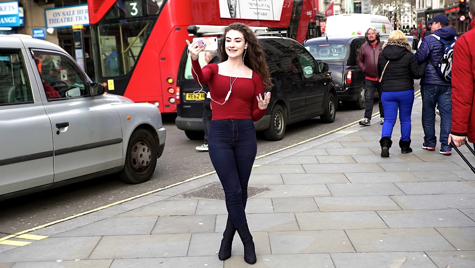 Internet Prankster,  Amber Doig-Thorne , tests out her Sennheiser AMBEO Smart Headset in London Piccadilly Circus