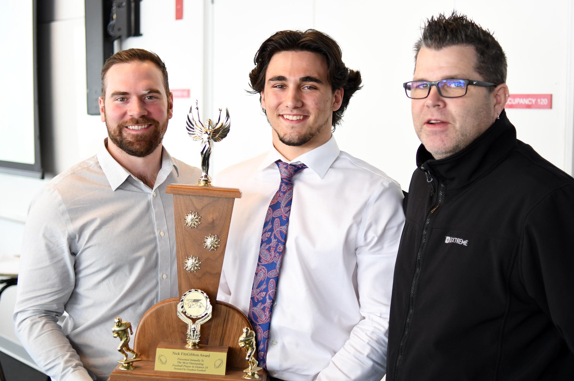 Former Gryphon great Nick FitzGibbon, left, with the winner of the Fitzy as most outstanding player in D10 football Tanner Nelmes, middle, and St. James coach Jeff Cummings.