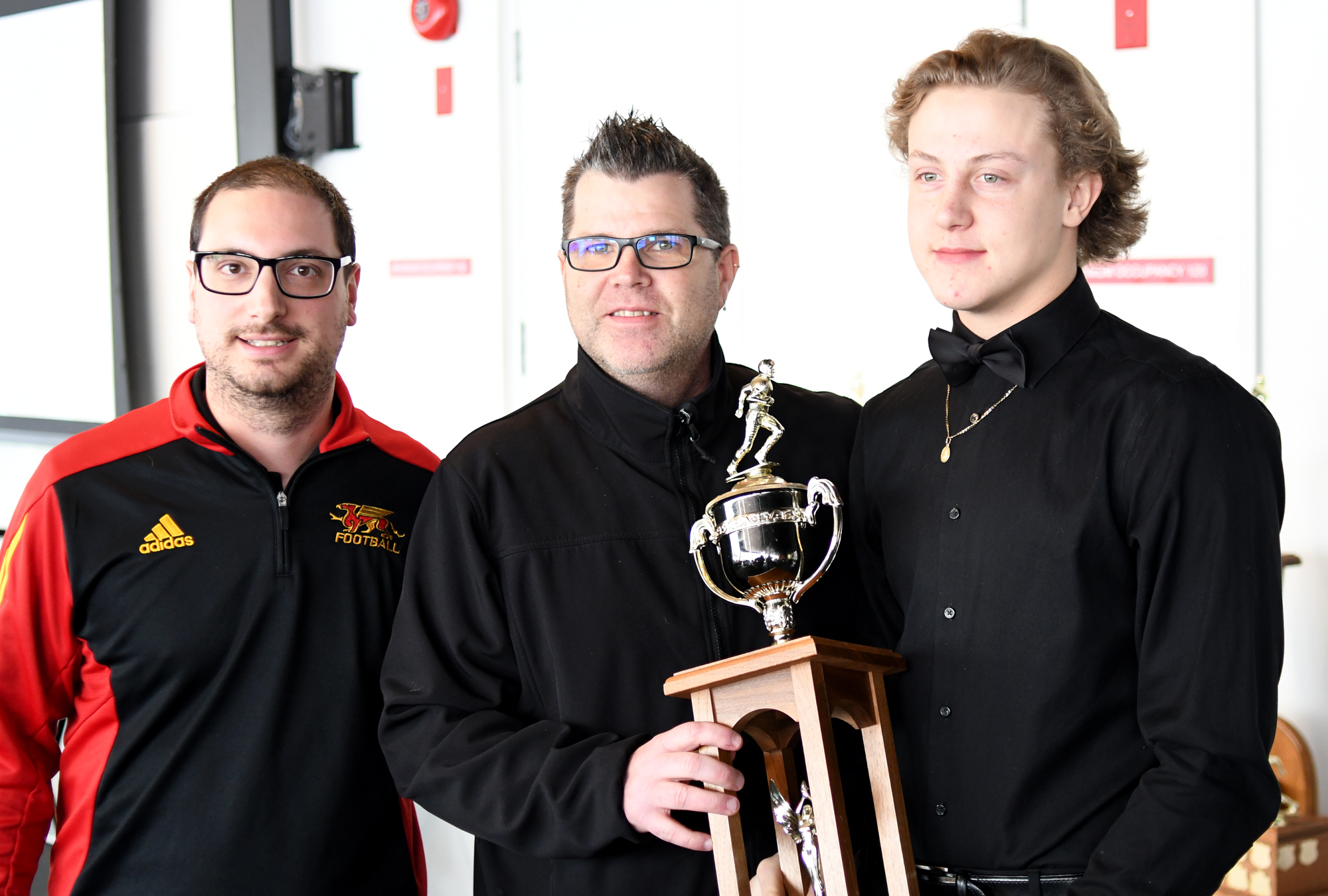 Gryphon Director of Football Operations Mike Aloisio, left, with St. James coach Jeff Cummings, middle, and defensive player of the year award winner Pawel Szymanski.