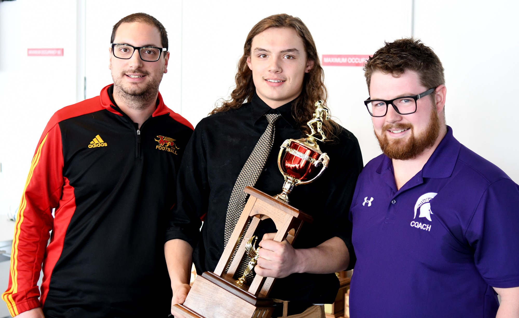 Gryphon Director of Football Operations Mike Aloisio, left, with offensive player of the year award winner Daniel Brown, middle, and Centennial coach Chas Douglas.