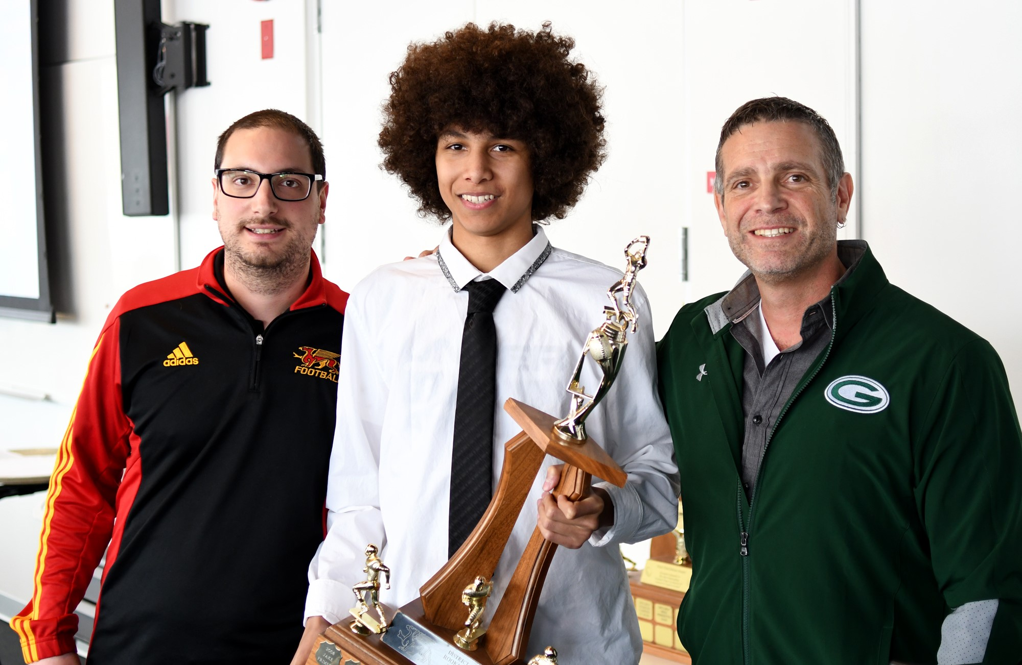 Gryphon Director of Football Operations Mike Aloisio, left, with rookie of the year award winner Keyon Robinson, middle, and Guelph CVI coach Dan Crabbe.